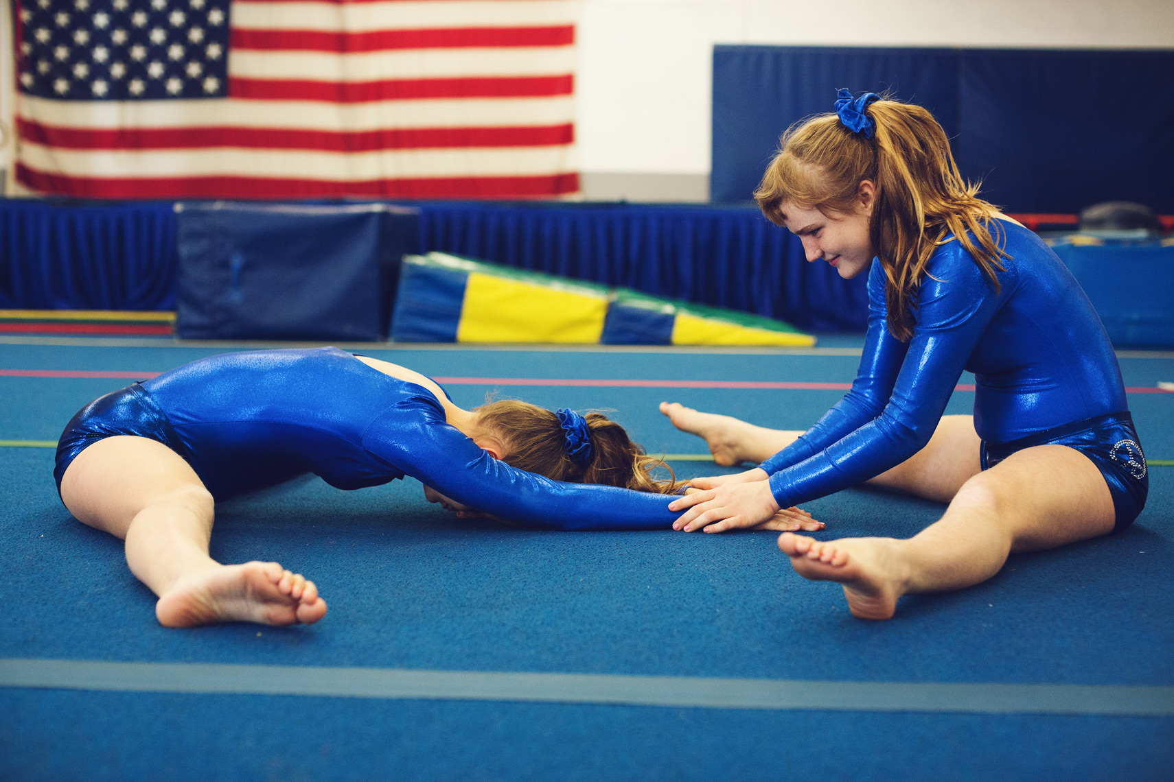 special olympics gymnast sisters stretching on blue mat, washington dc commercial photography