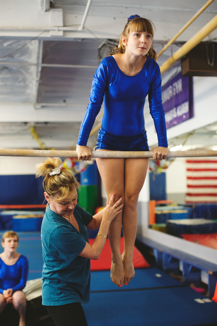young female special olympics gymnast on gymnastics bar with trainer, washington dc commercial photography