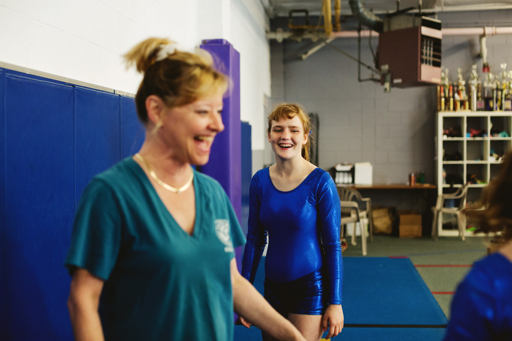young female special olympics gymnast in blue laughing with trainer, washington dc commercial photography