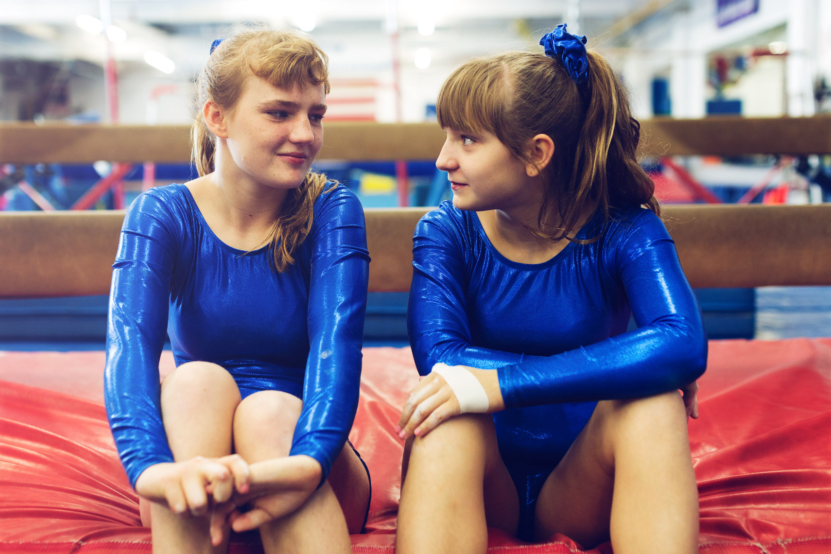 special olympics gymnast sisters sitting on red mat, washington dc commercial photography