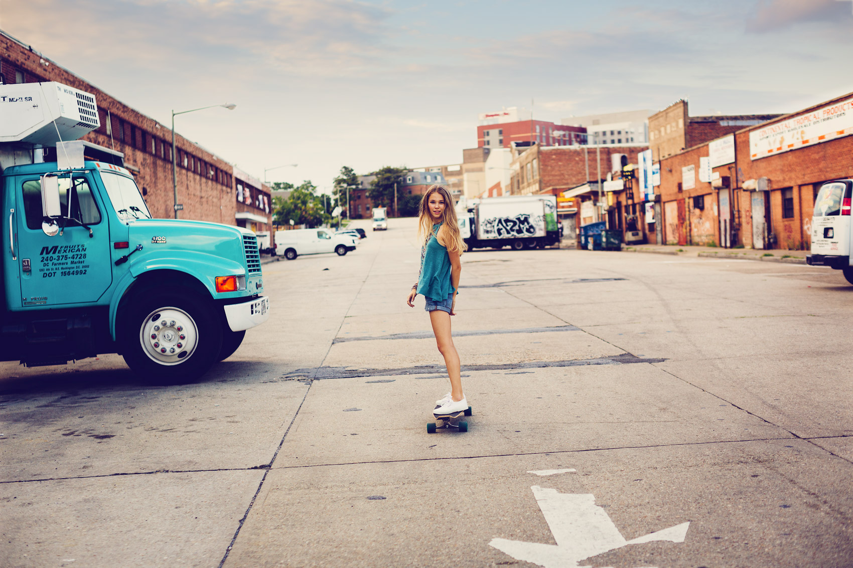 teenage girl skateboarding industrial area for washington dc advertising photography
