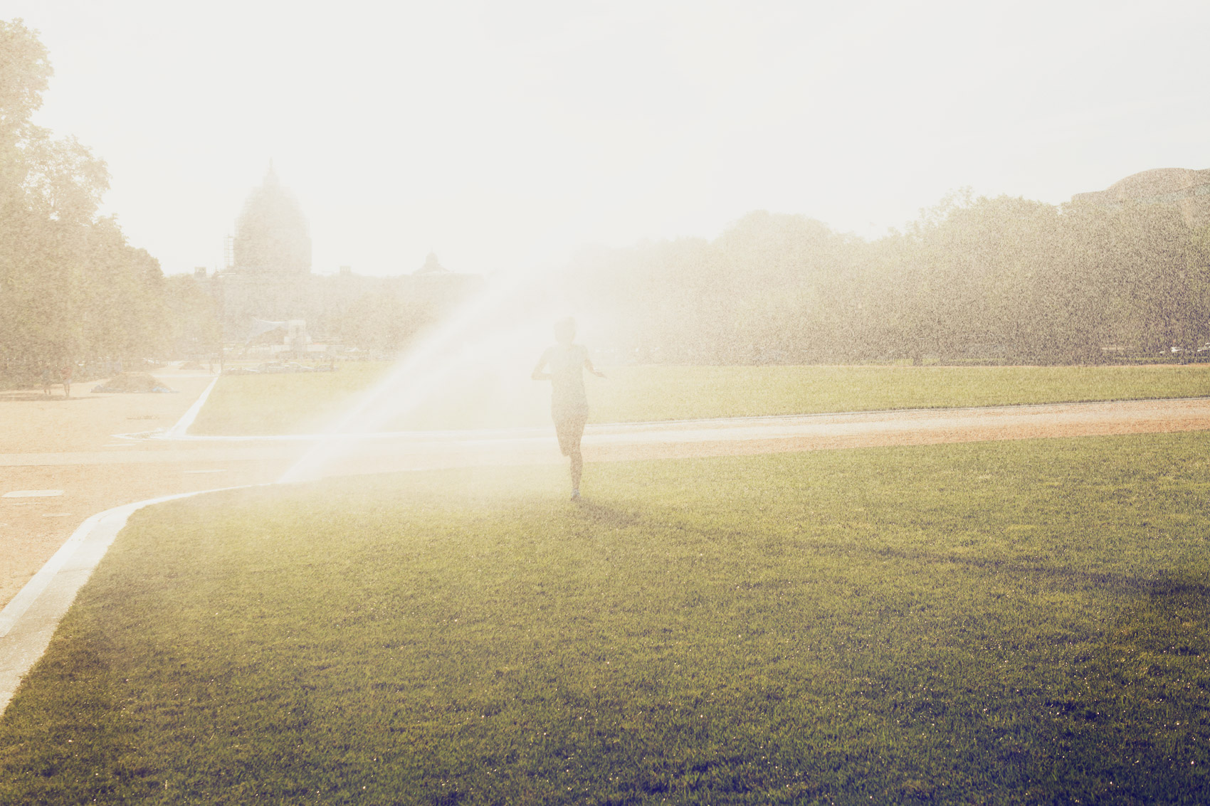 woman running through national mall sprinkler for washington dc commercial photography