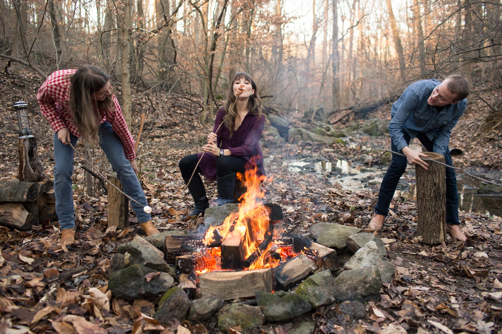 shaed sits by campfire in forest for washington dc commercial photography