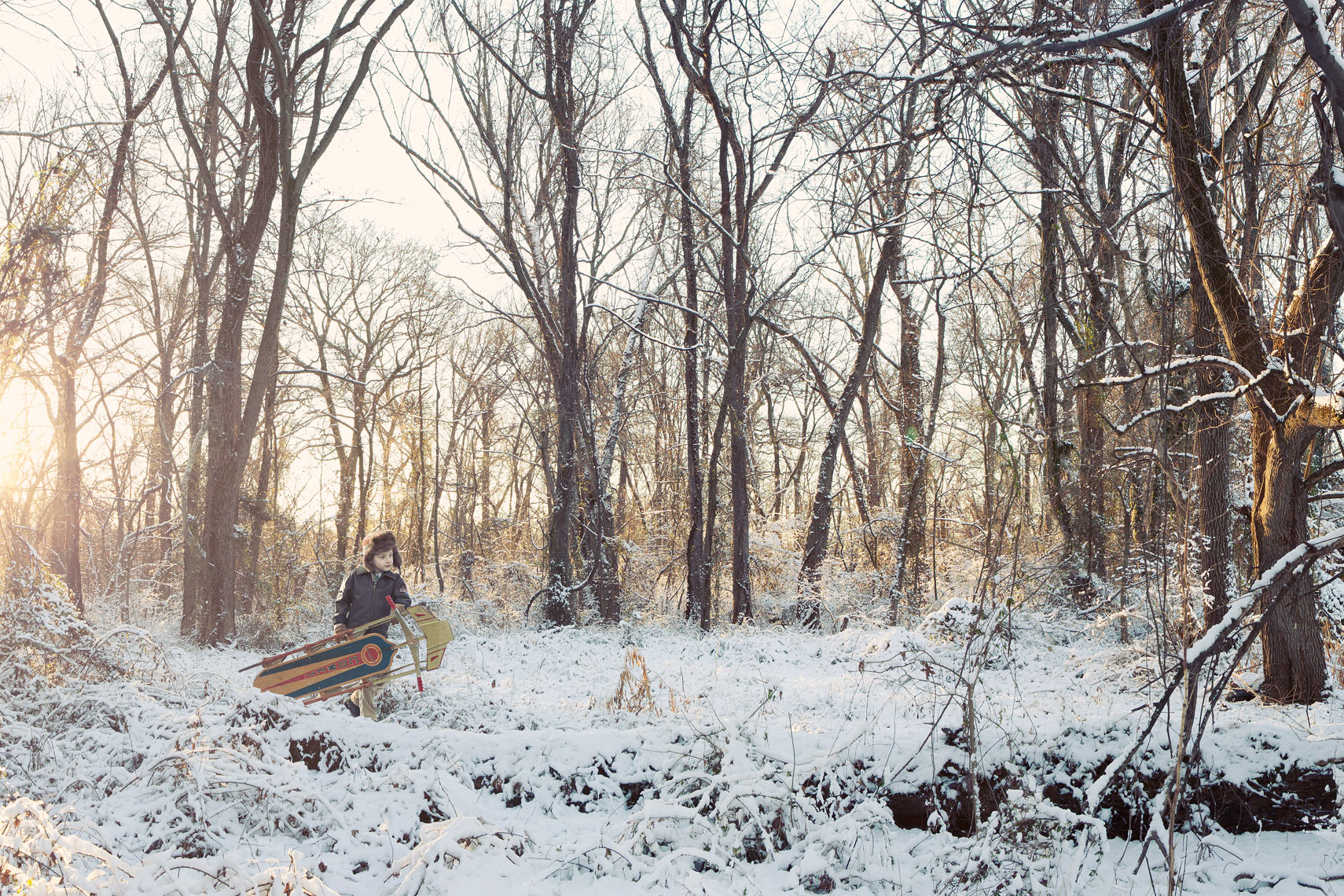 boy carries sled in snowy forest for washington dc commercial photography