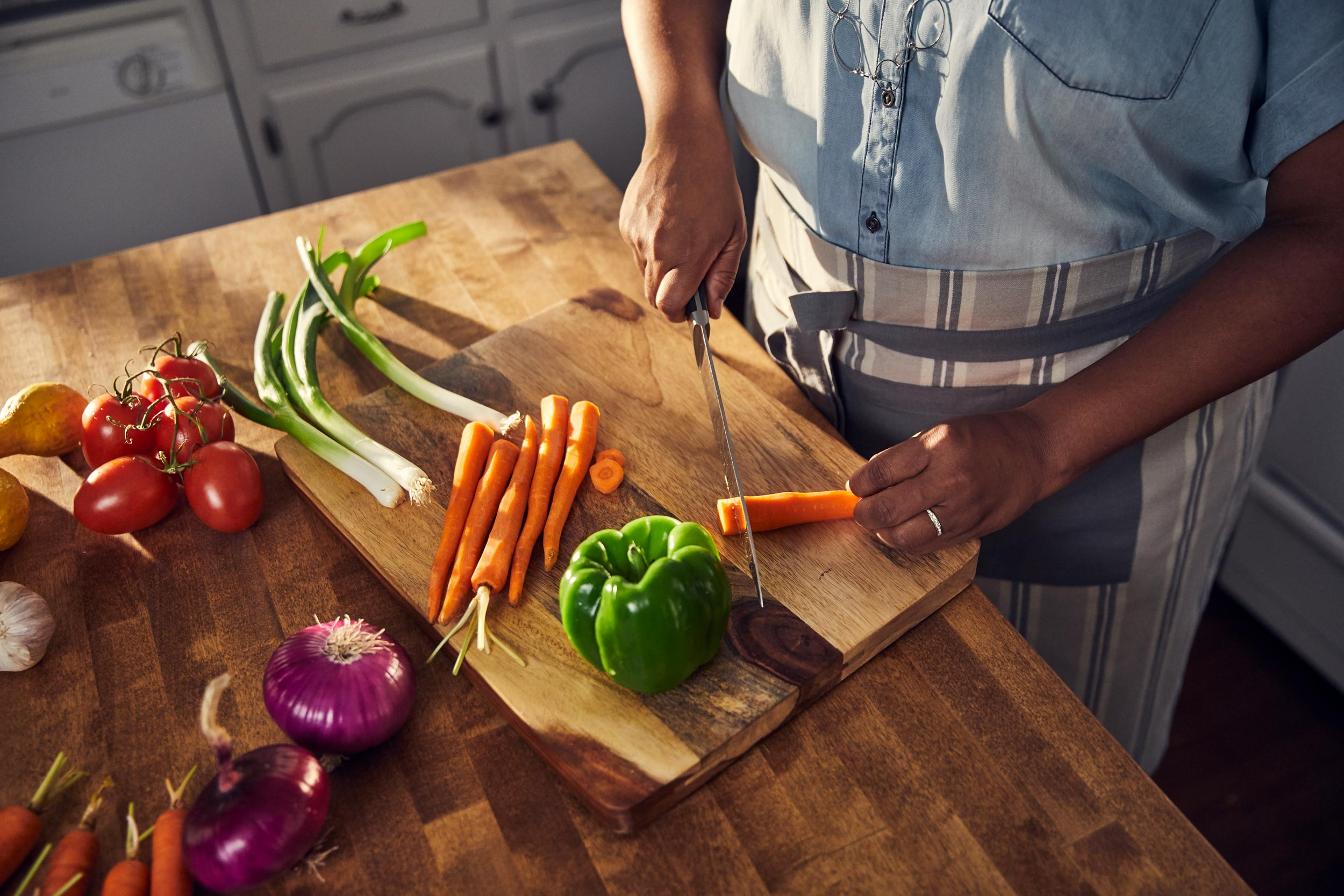 hands cutting carrot on cutting board, washington dc commercial photography