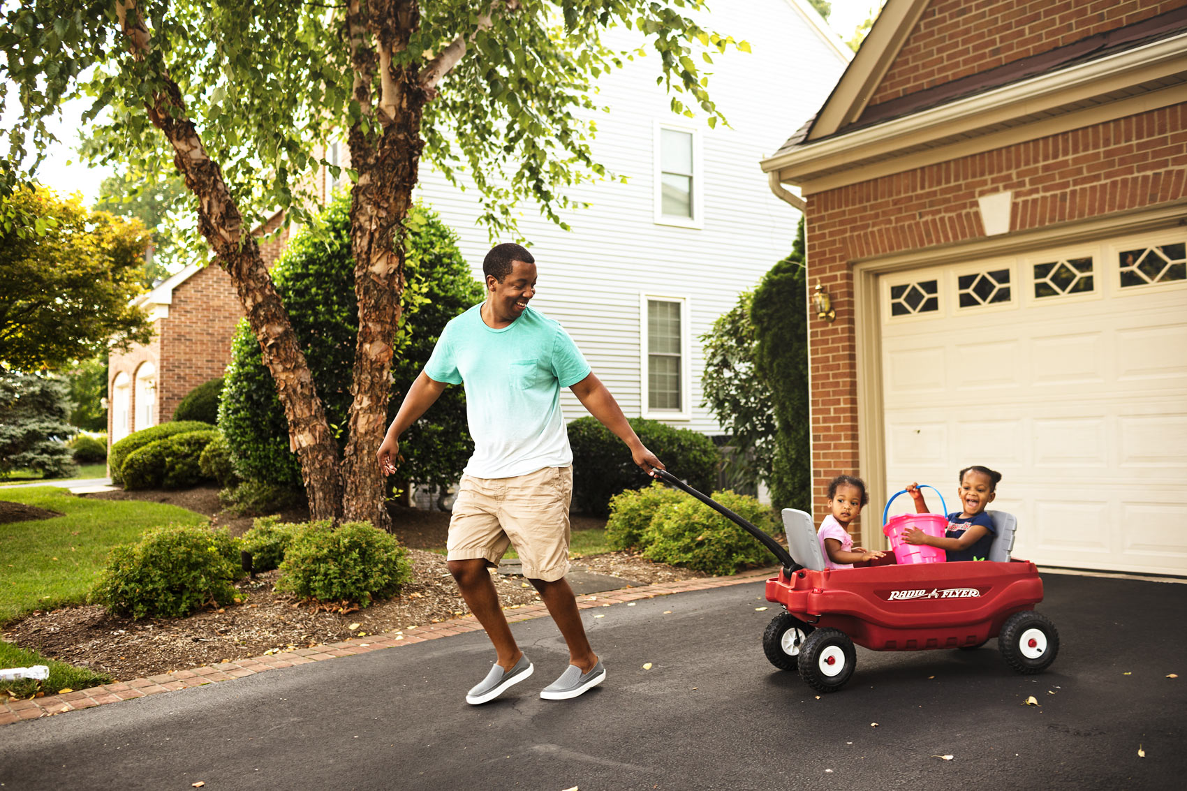 father pulling daughters in red radio flyer wagon in driveway , washington dc commercial photography