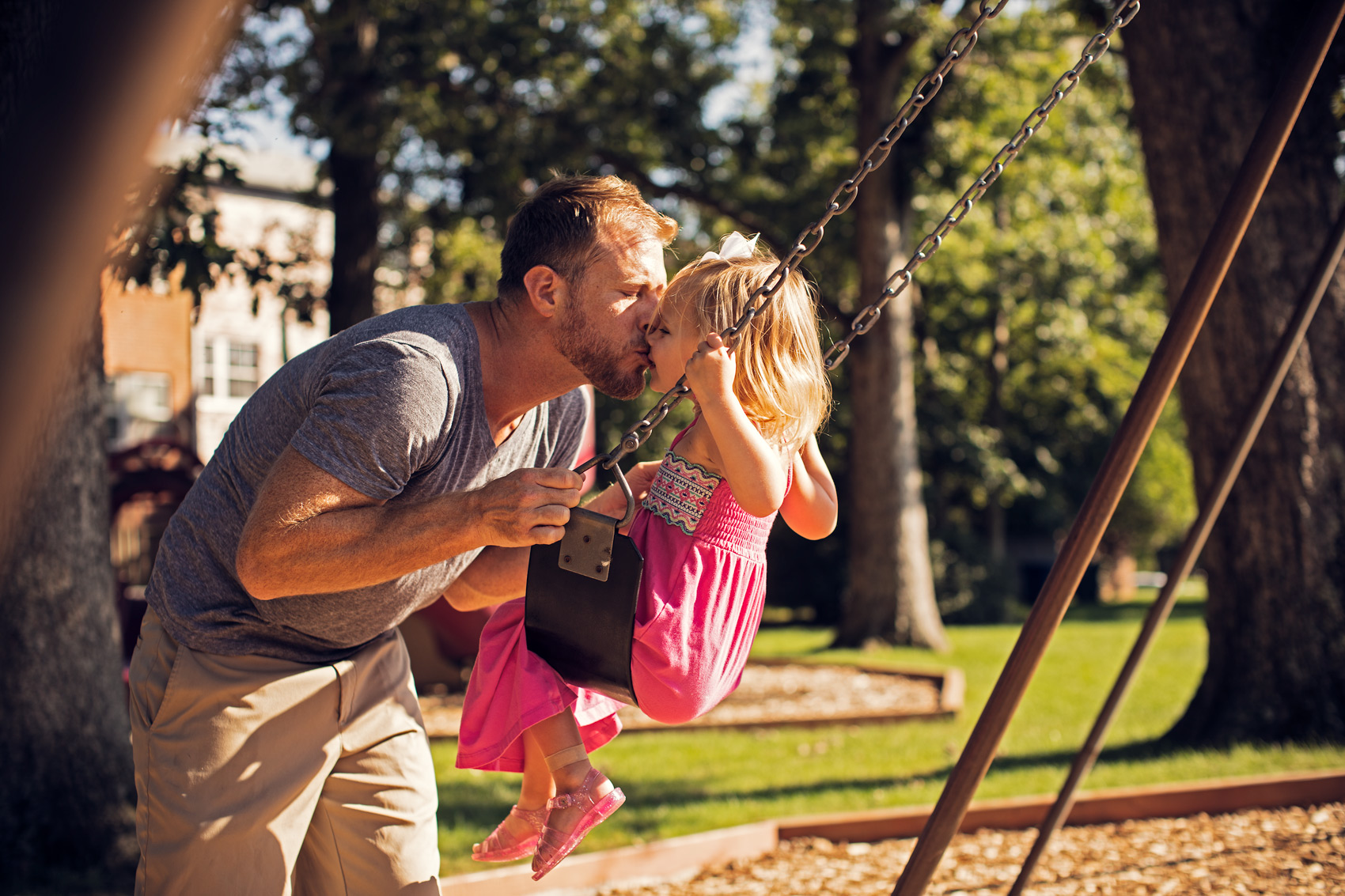 dad kissing young daughter on swing in park, washington dc commercial photography