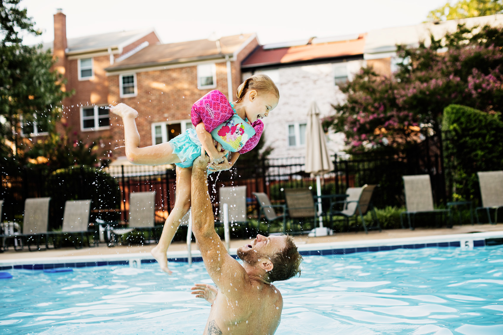 father holding up daughter with floaties in pool, washington dc commercial photography