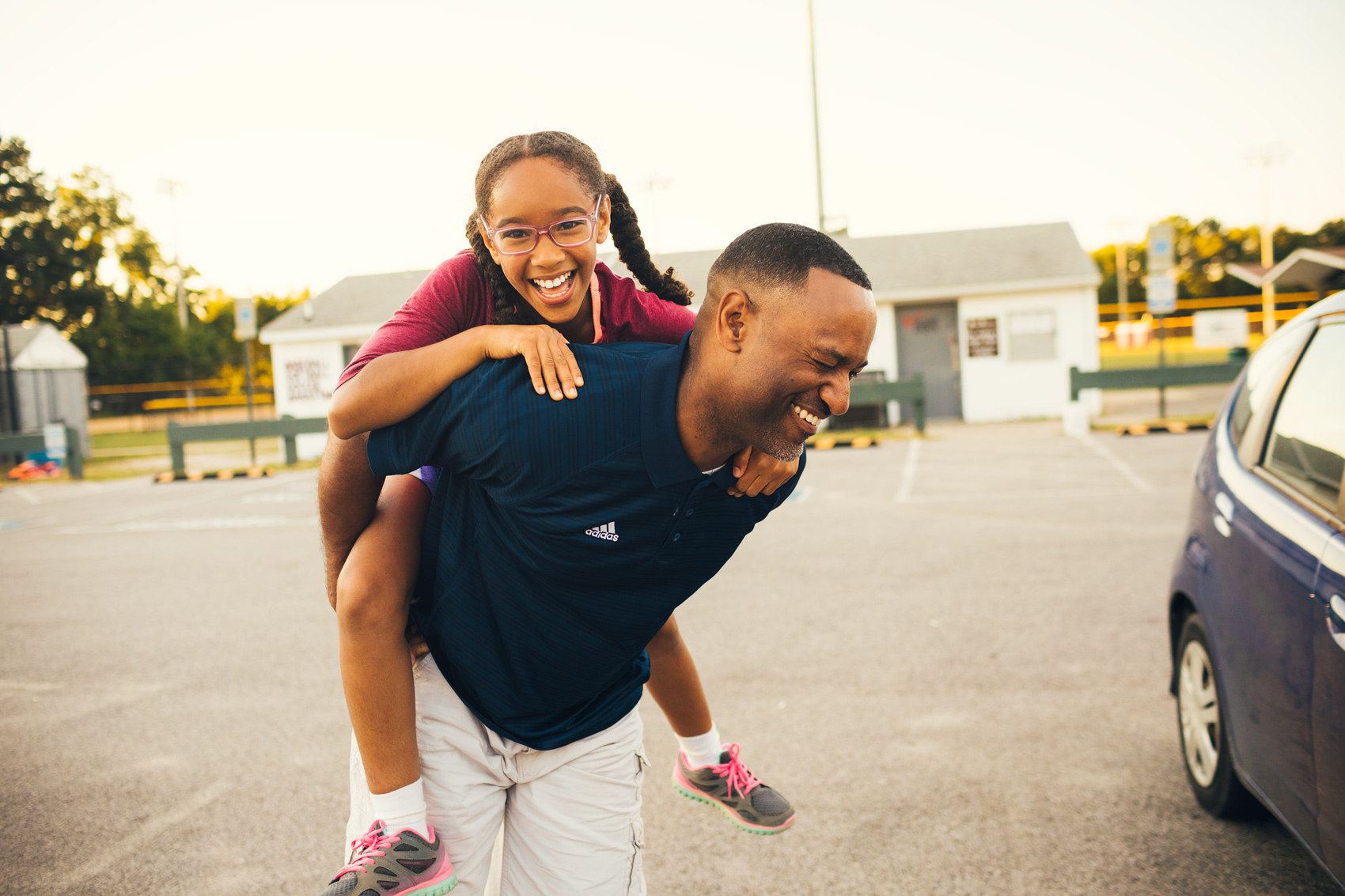 girl piggyback riding father in parking lot, washington dc commercial photography