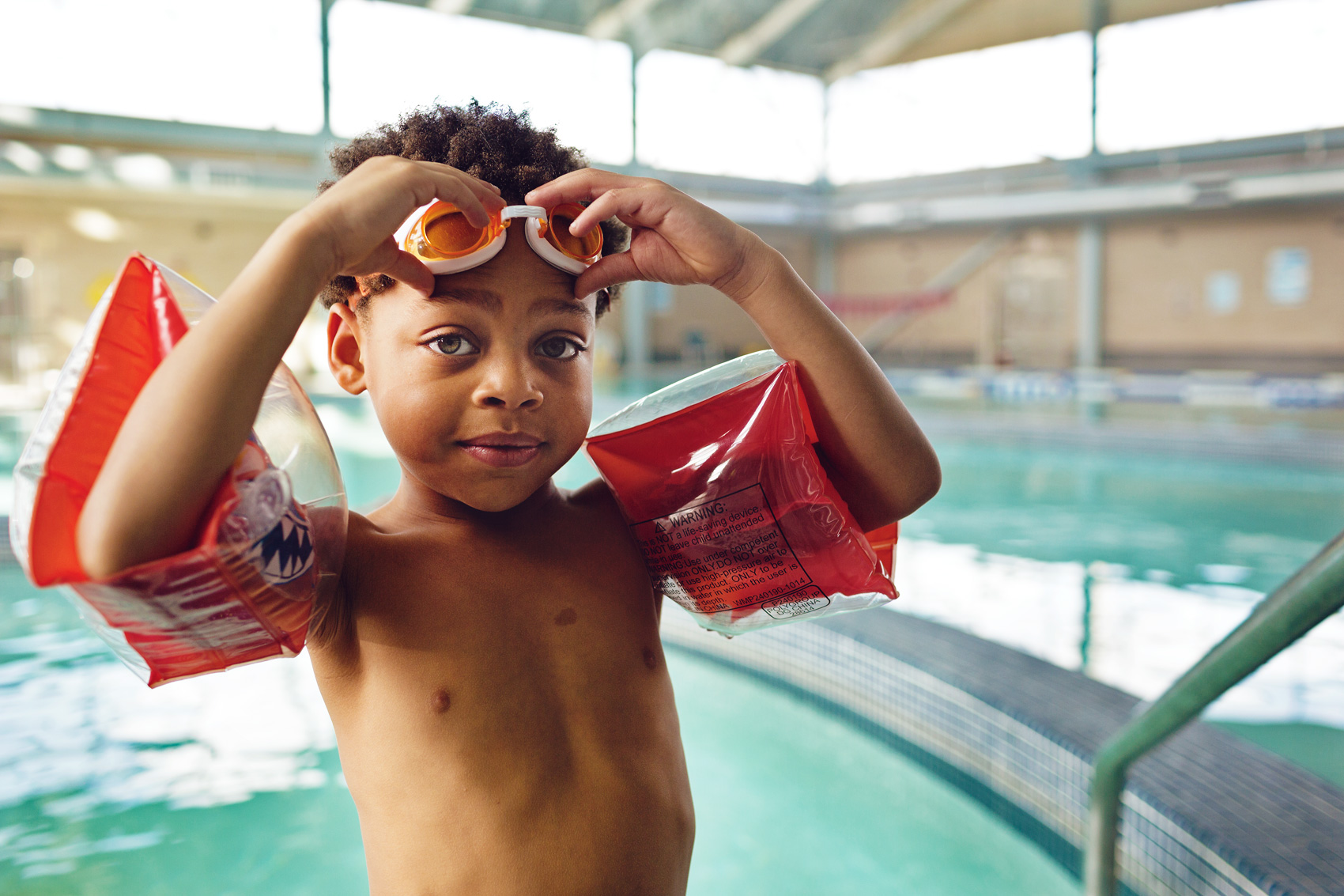boy with floaties putting on goggles by a pool washington dc commercial photograpy