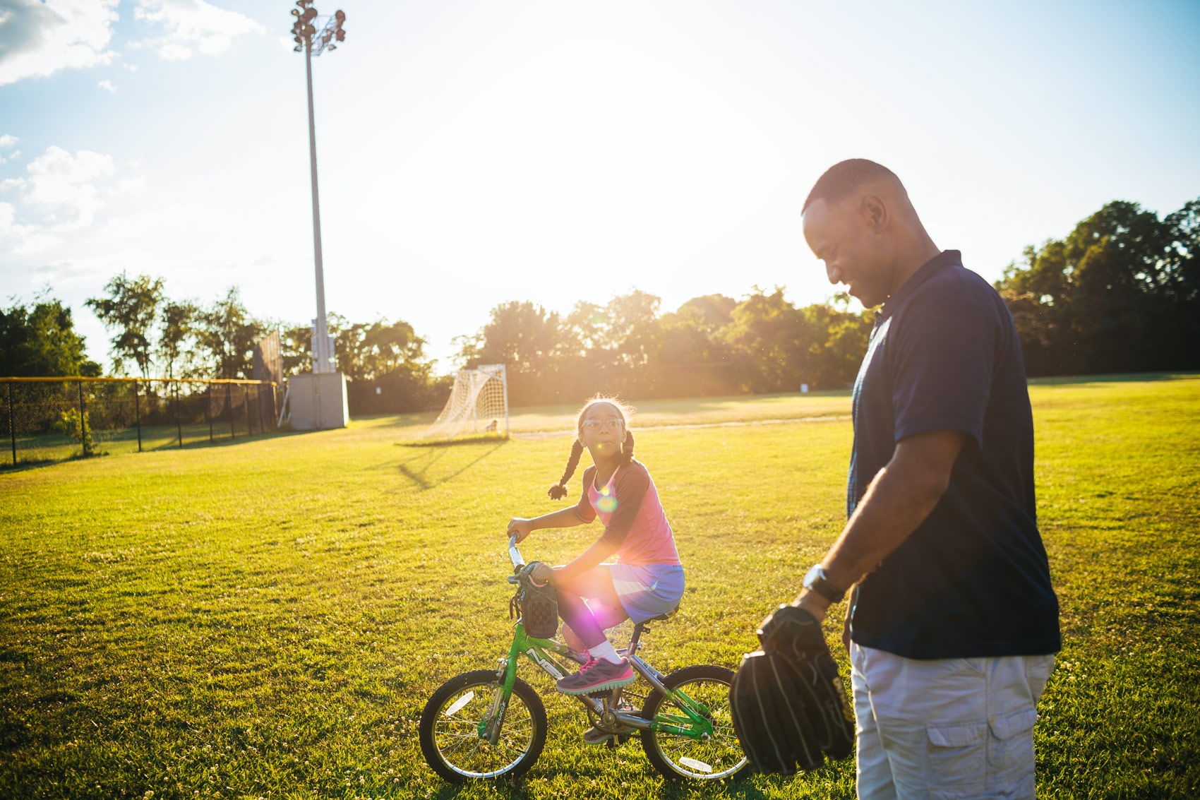 daughter riding on bicycle with father to softball practice, washington dc commercial photography