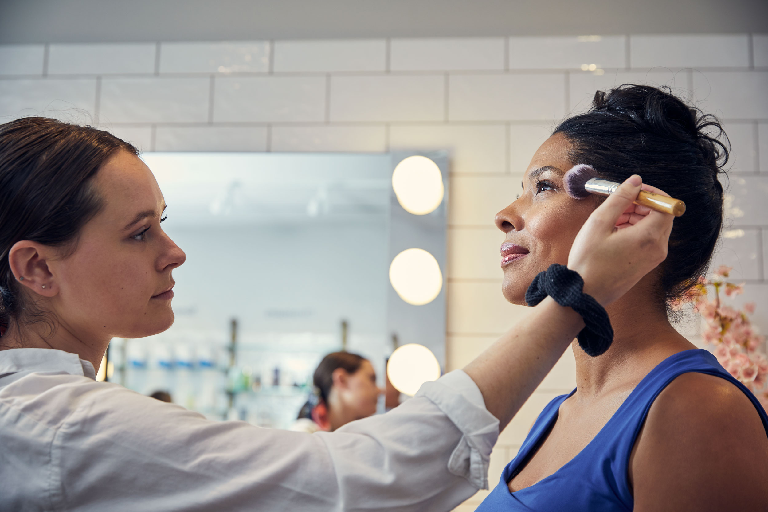 woman applying makeup on adult woman, washington dc commercial photography