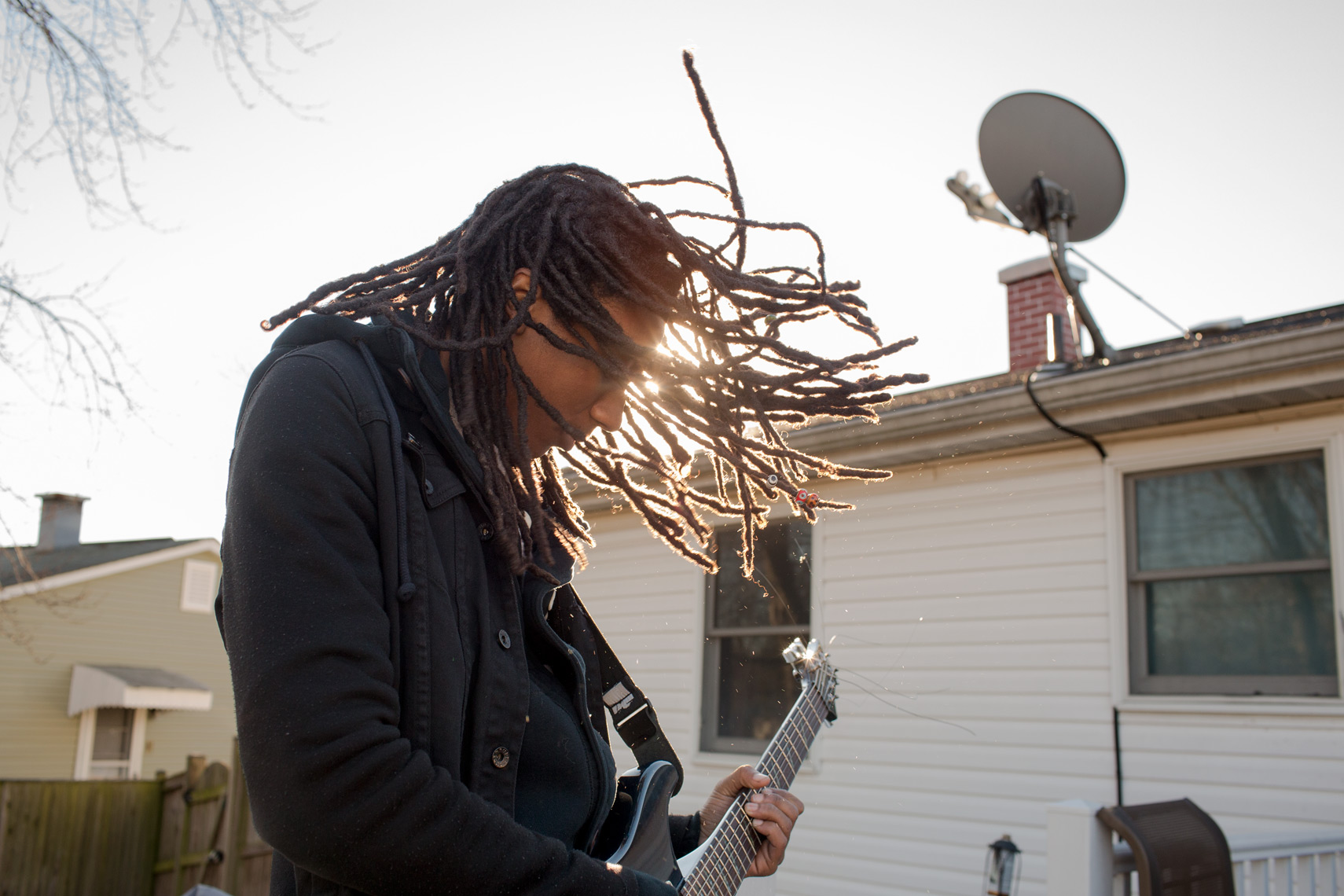 dreadlocks thrashing while teenage boy plays guitar for washington dc commercial photography