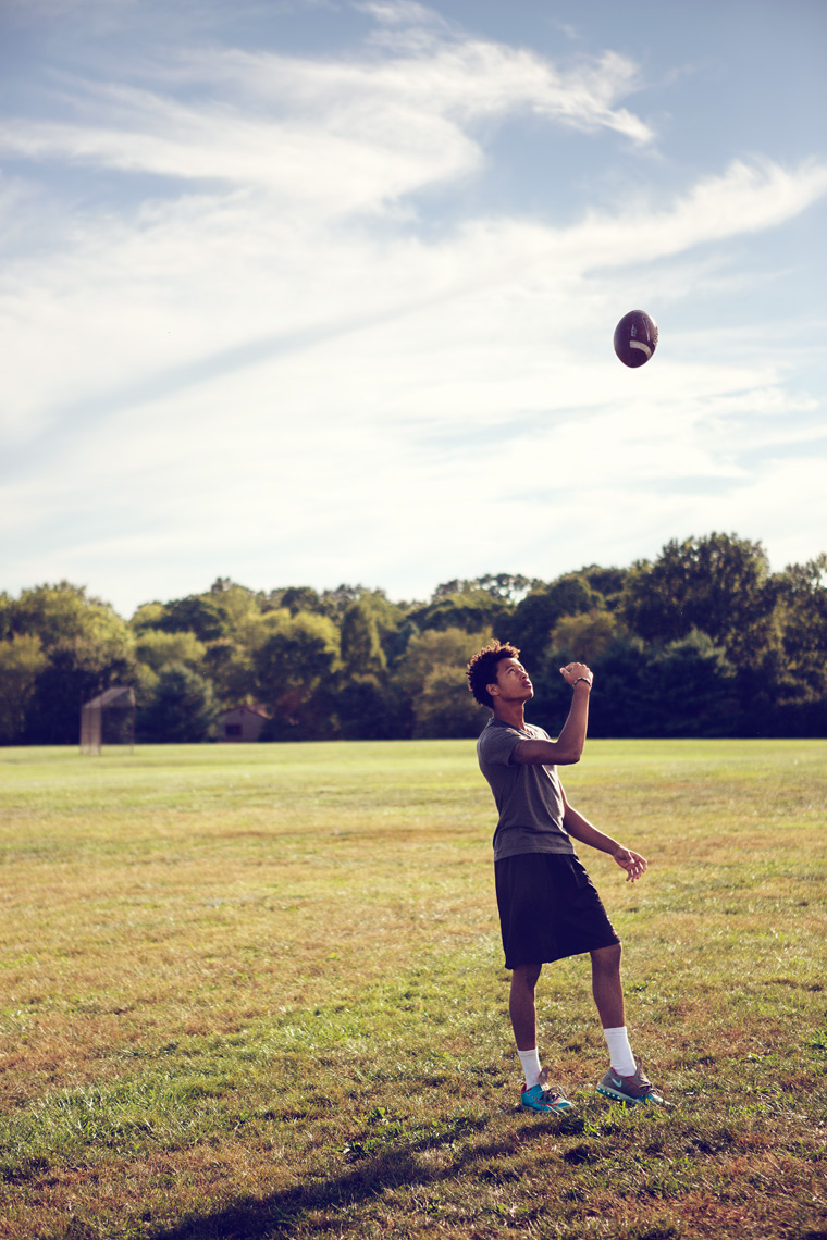 high school football tossing ball in the air for washington dc commercial photography