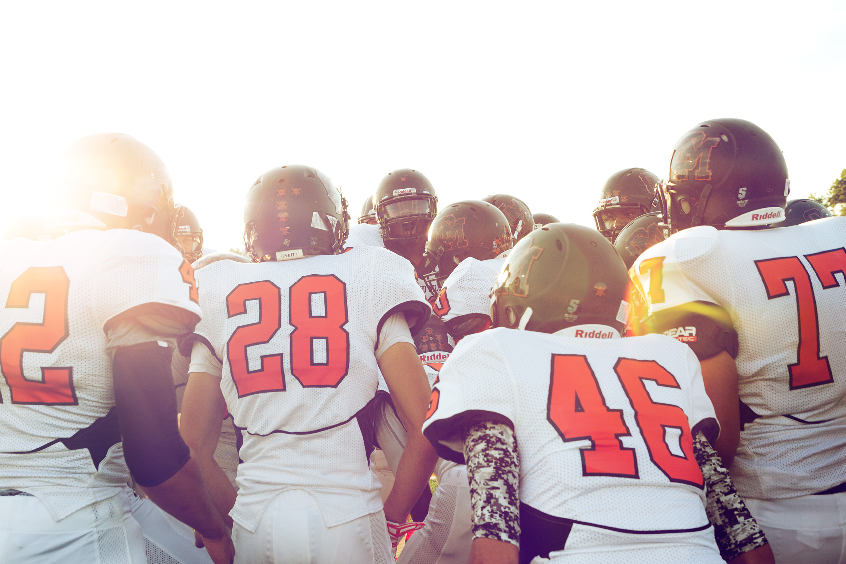 high school football team huddling for washington dc commercial photography