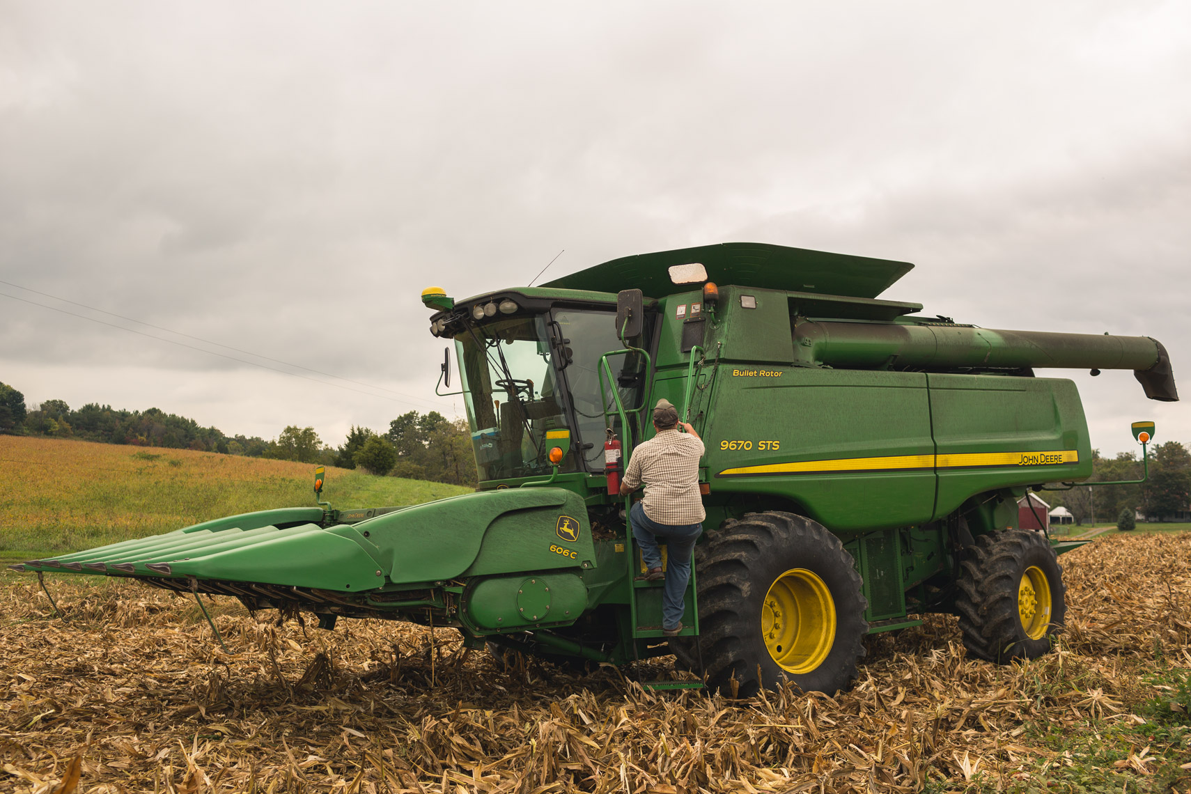 farmer climbing down john deere harvester for washington dc industrial photography