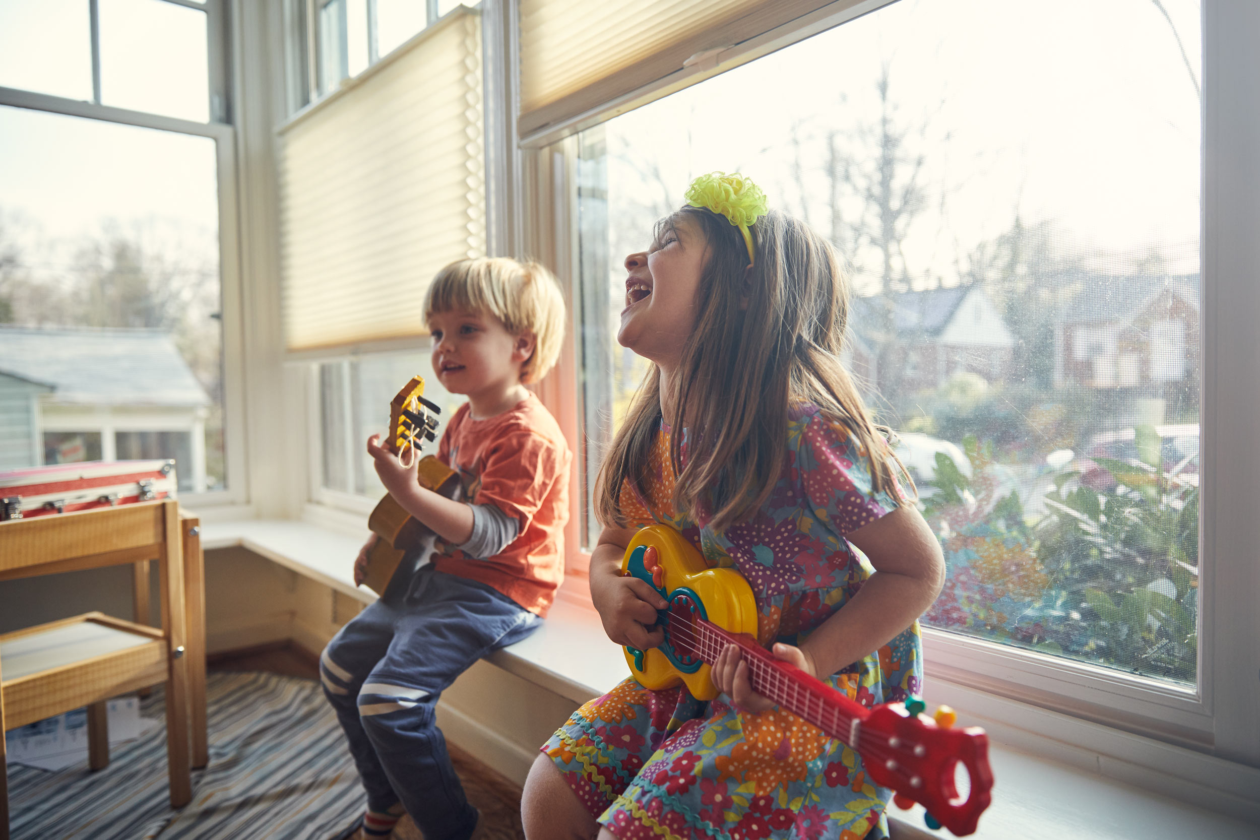 toddlers playing guitars by window window for washington dc commercial photography