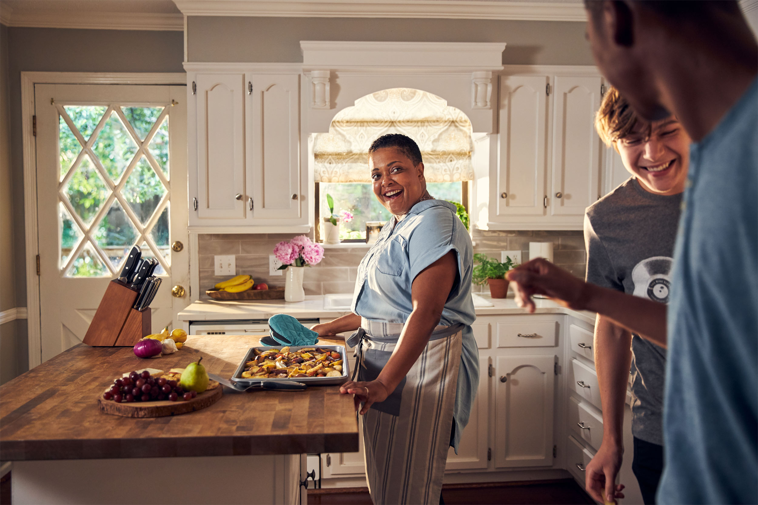 teens swiping food from kitchen with mom, washington dc commercial photography