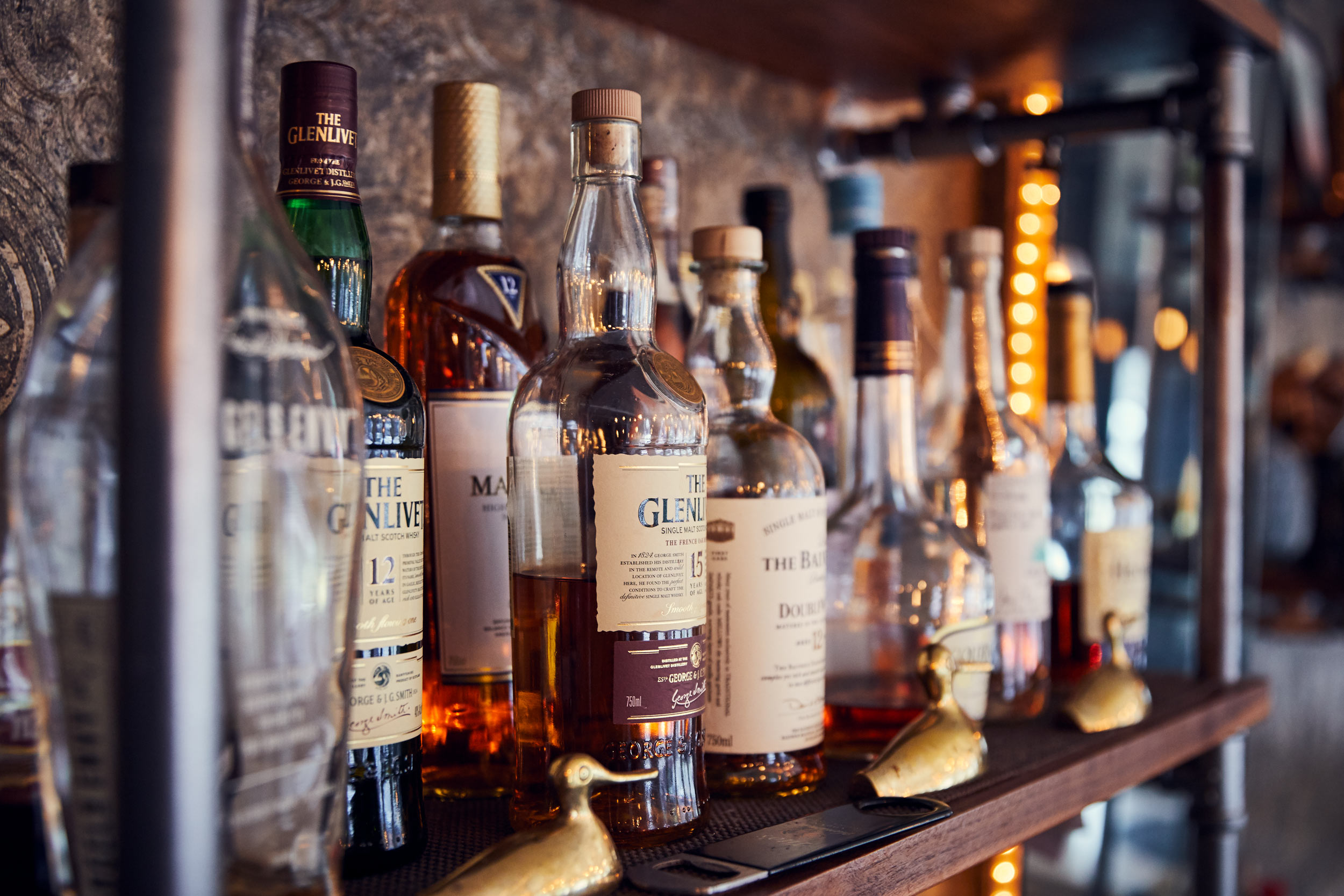 liquor shelf with whiskey and small ducks, washington dc commercial photography