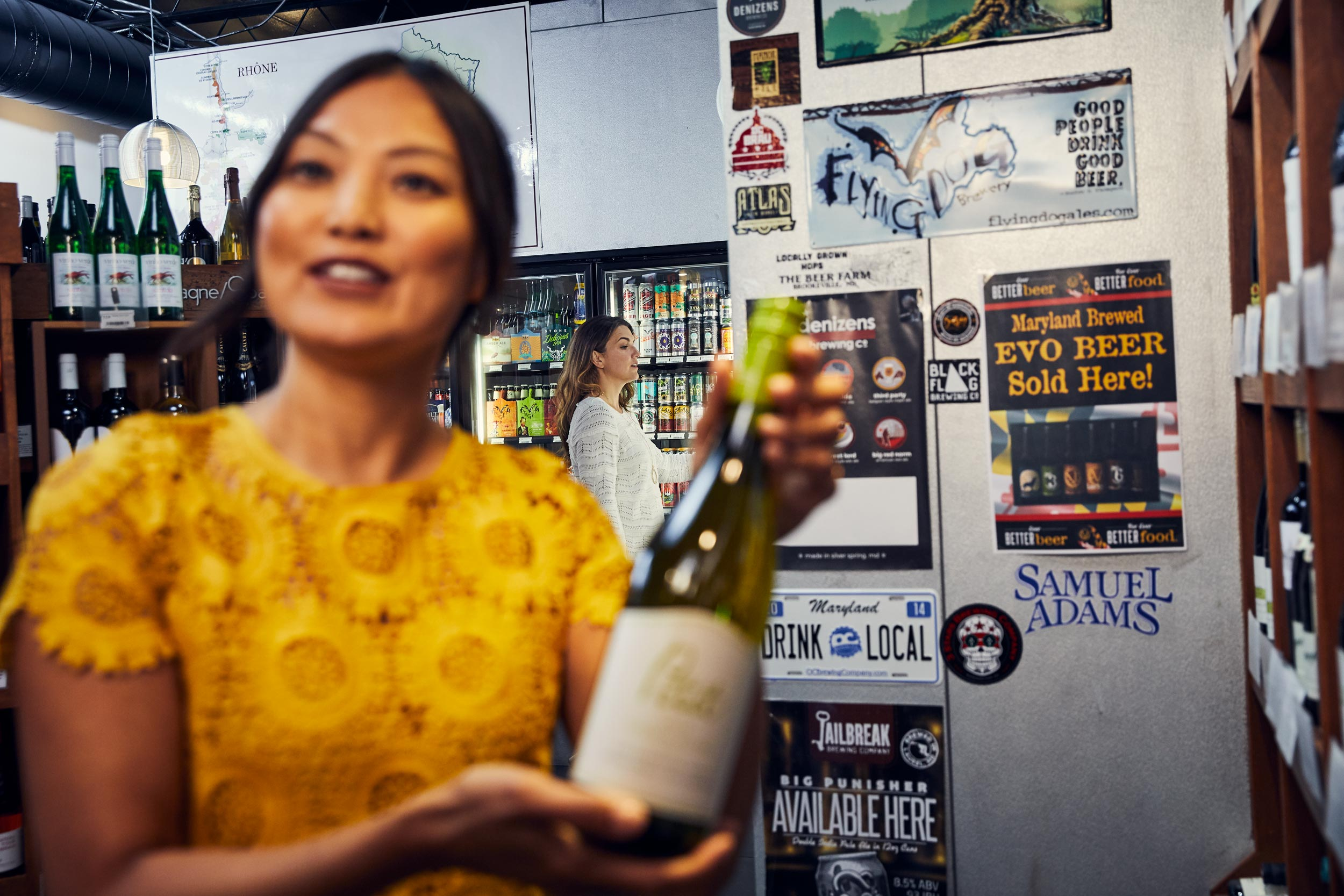 woman in yellow dress holding wine bottle in liquor store, washington dc commercial photography
