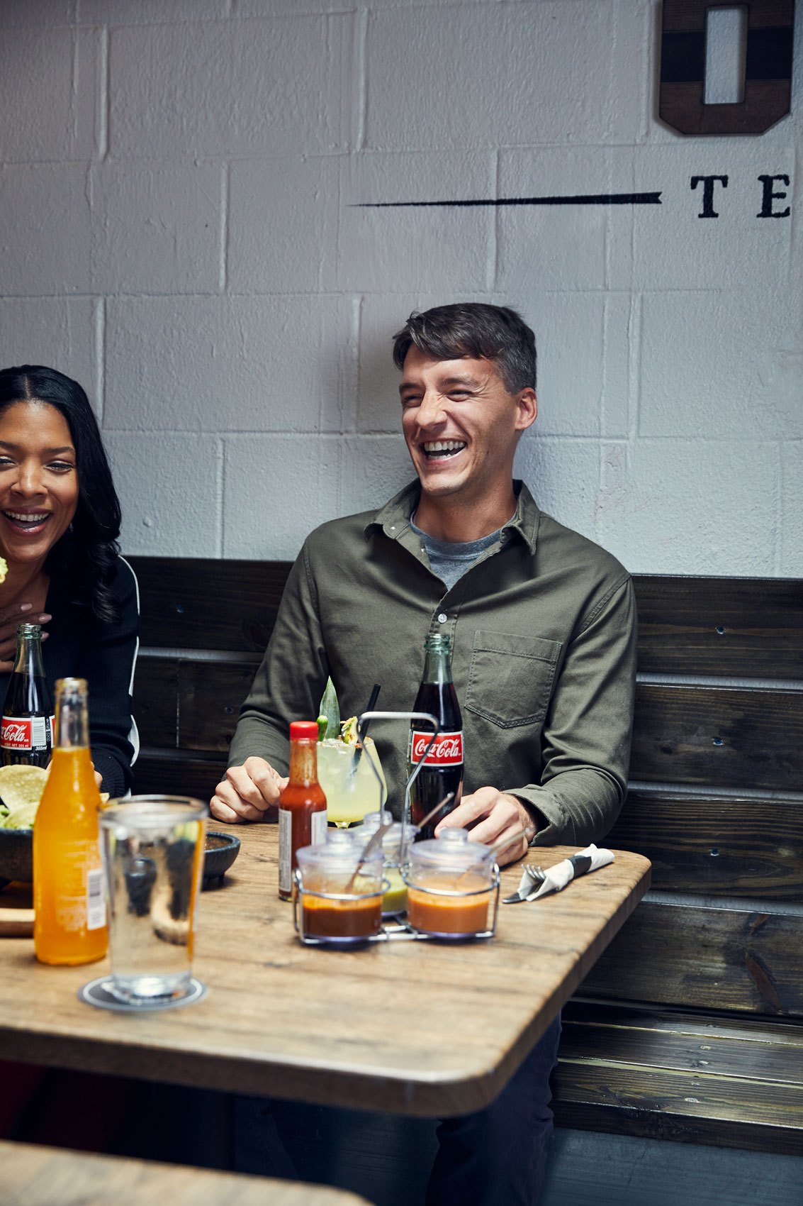 man and woman laughing with coca-cola bottles in restaurant, washington dc commercial photography