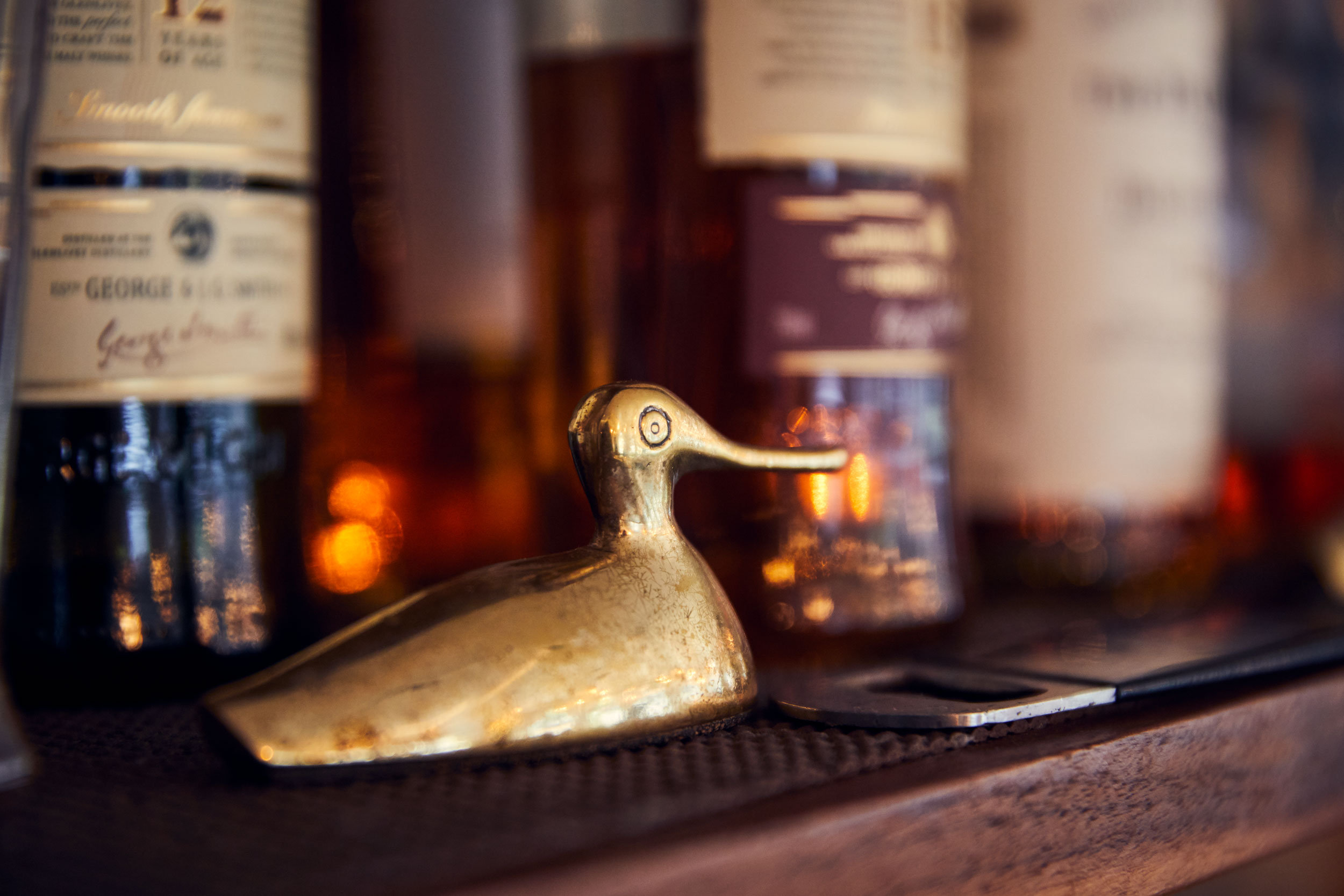 metal duck and whiskey on a shelf, washington dc commercial  photography