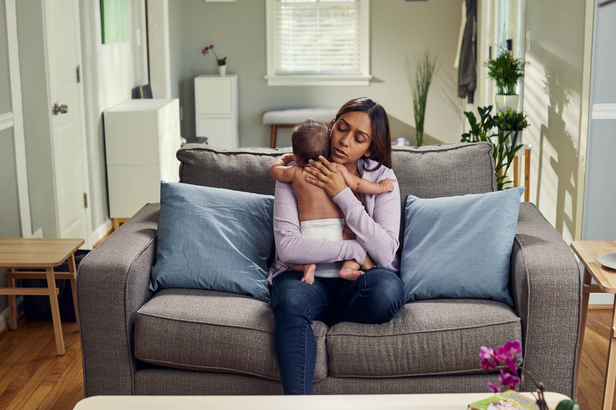 mom comforting baby on couch in living room, washington dc commercial photography