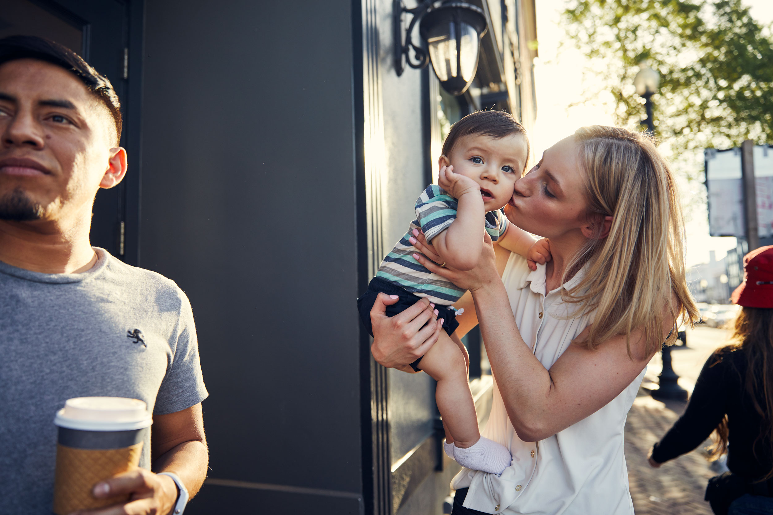 mom kissing baby on street for washington dc commercial photography
