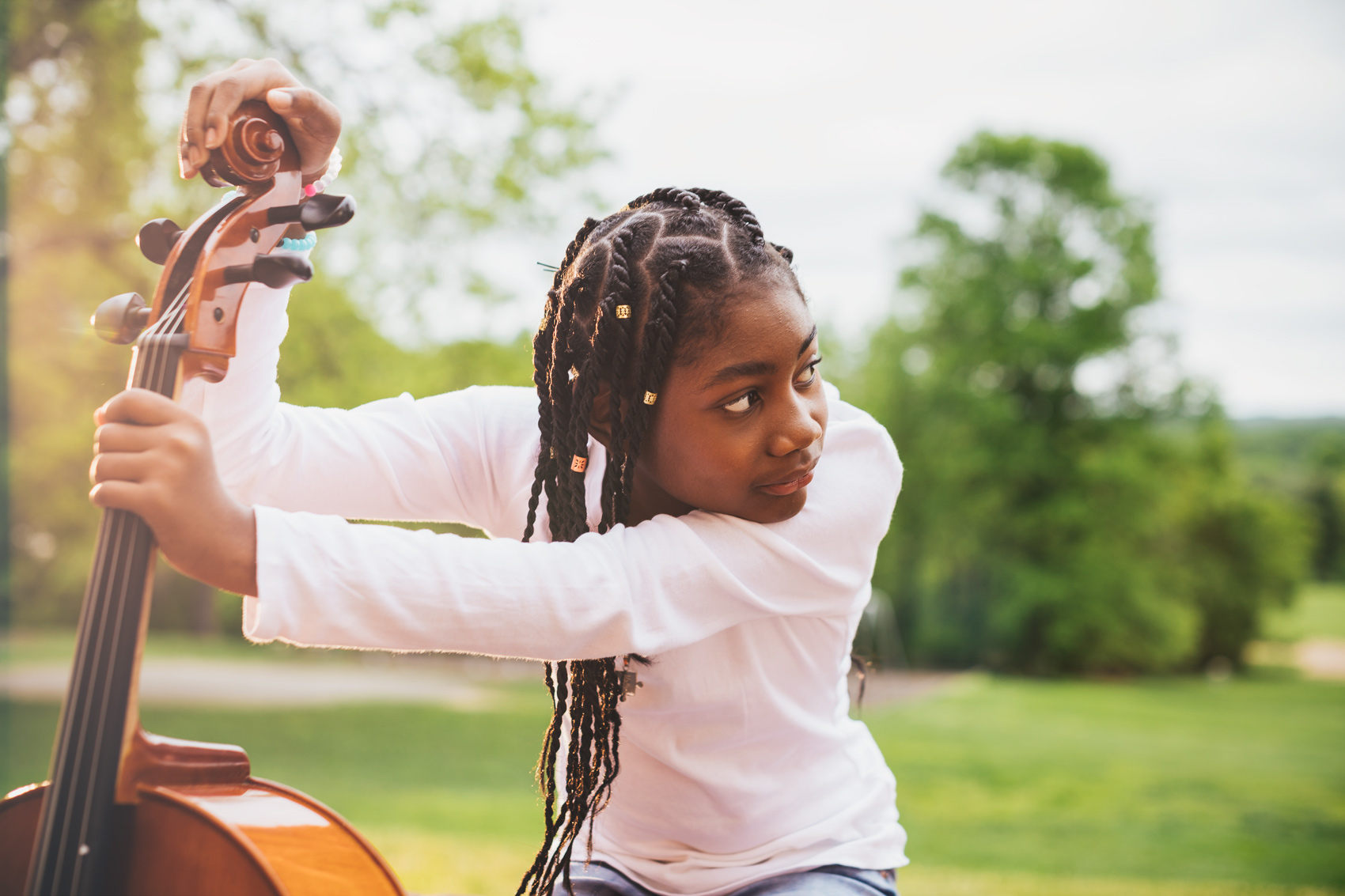 adolescent girl holding cello fingerboard outside, washington dc commercial photography