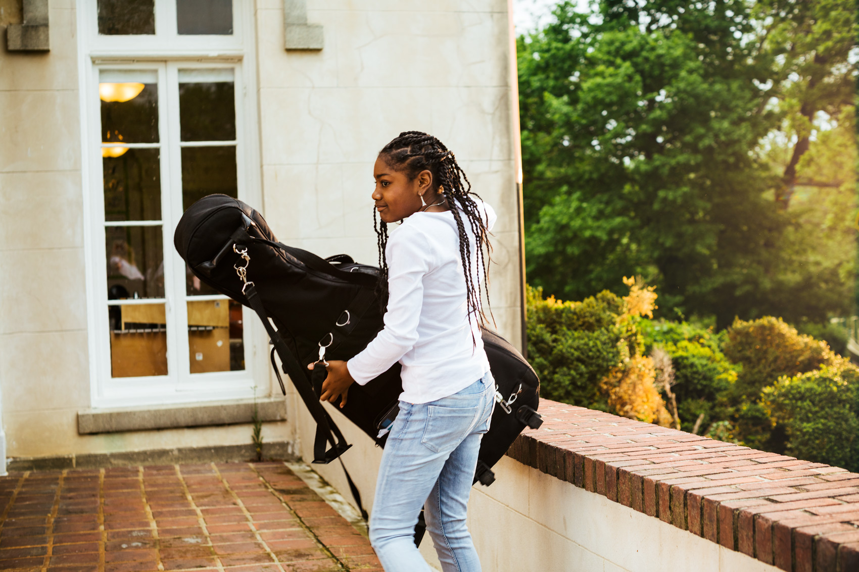 adolescent girl carrying cello case outside, washington dc commercial photography