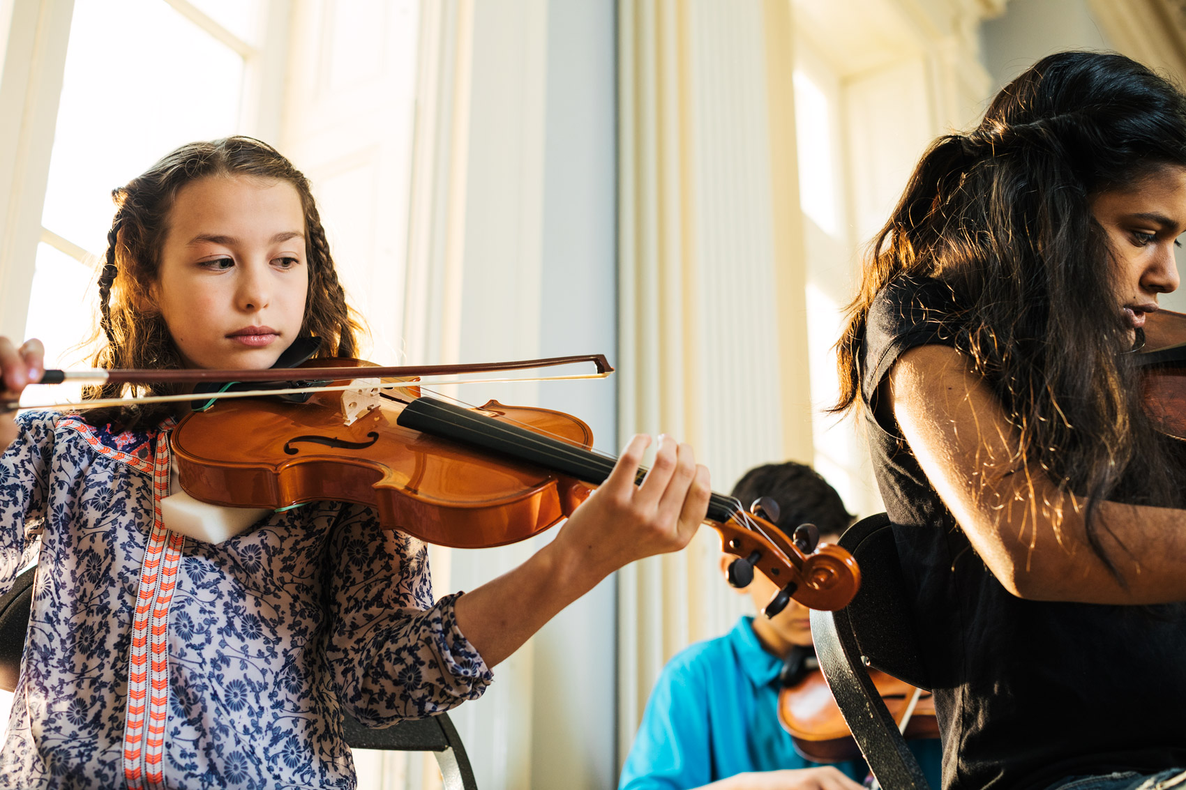 adolescent kids playing violins inside by window, washington dc commercial photography