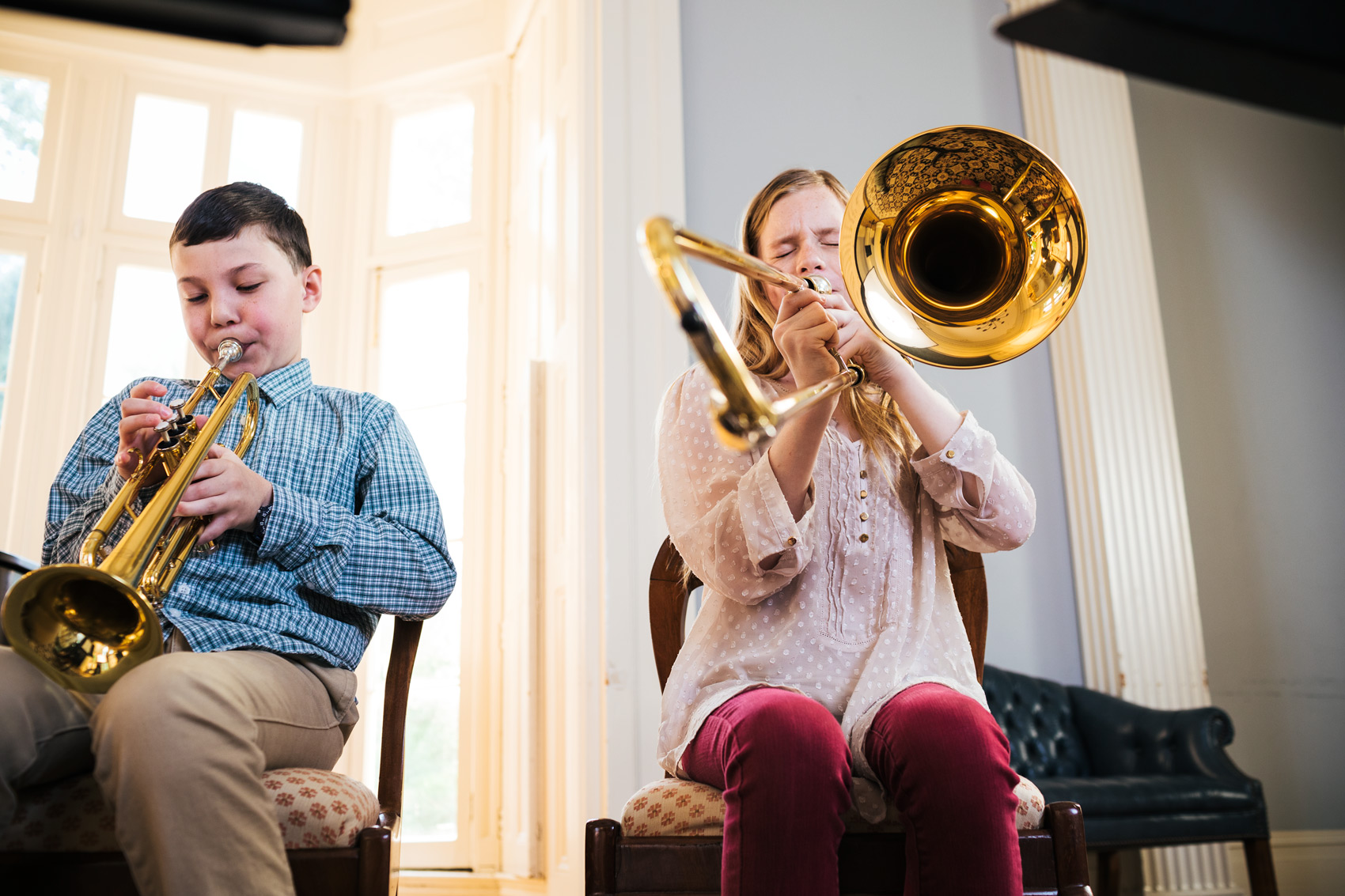 boy and girl playing horns by window, washington dc commercial photography