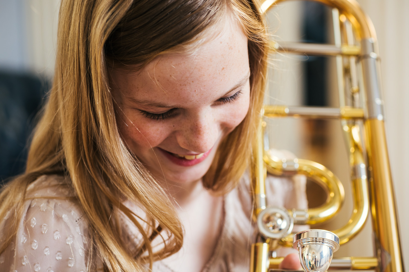 tween girl laughing with trombone, washington dc commercial photography