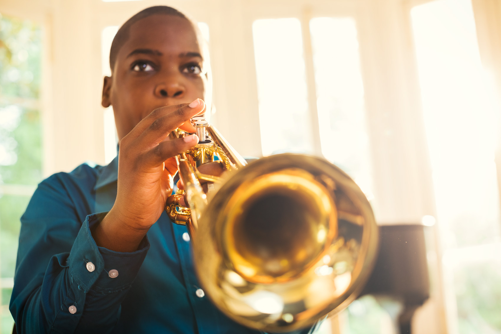 adolescent boy playing trumpet by window, washington dc commercial photography