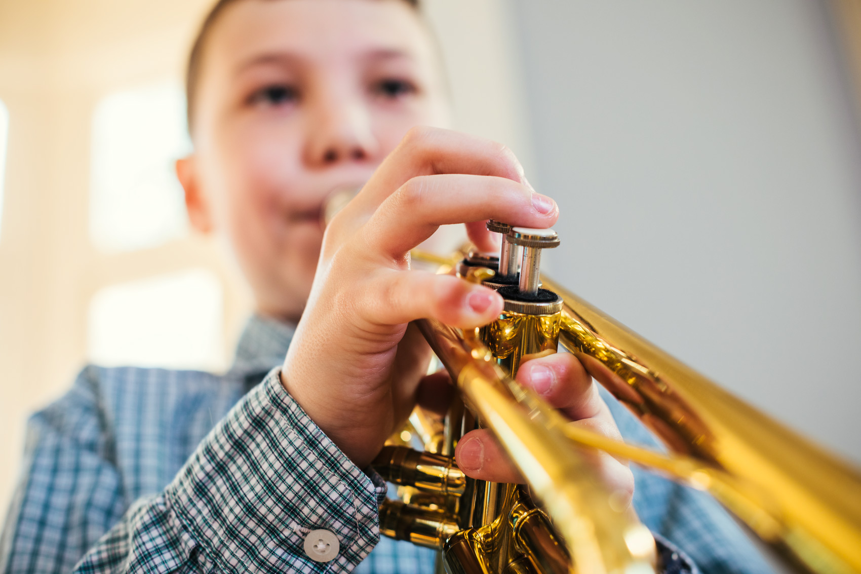 adolescent boy playing trumpet keys, washington dc commercial photography