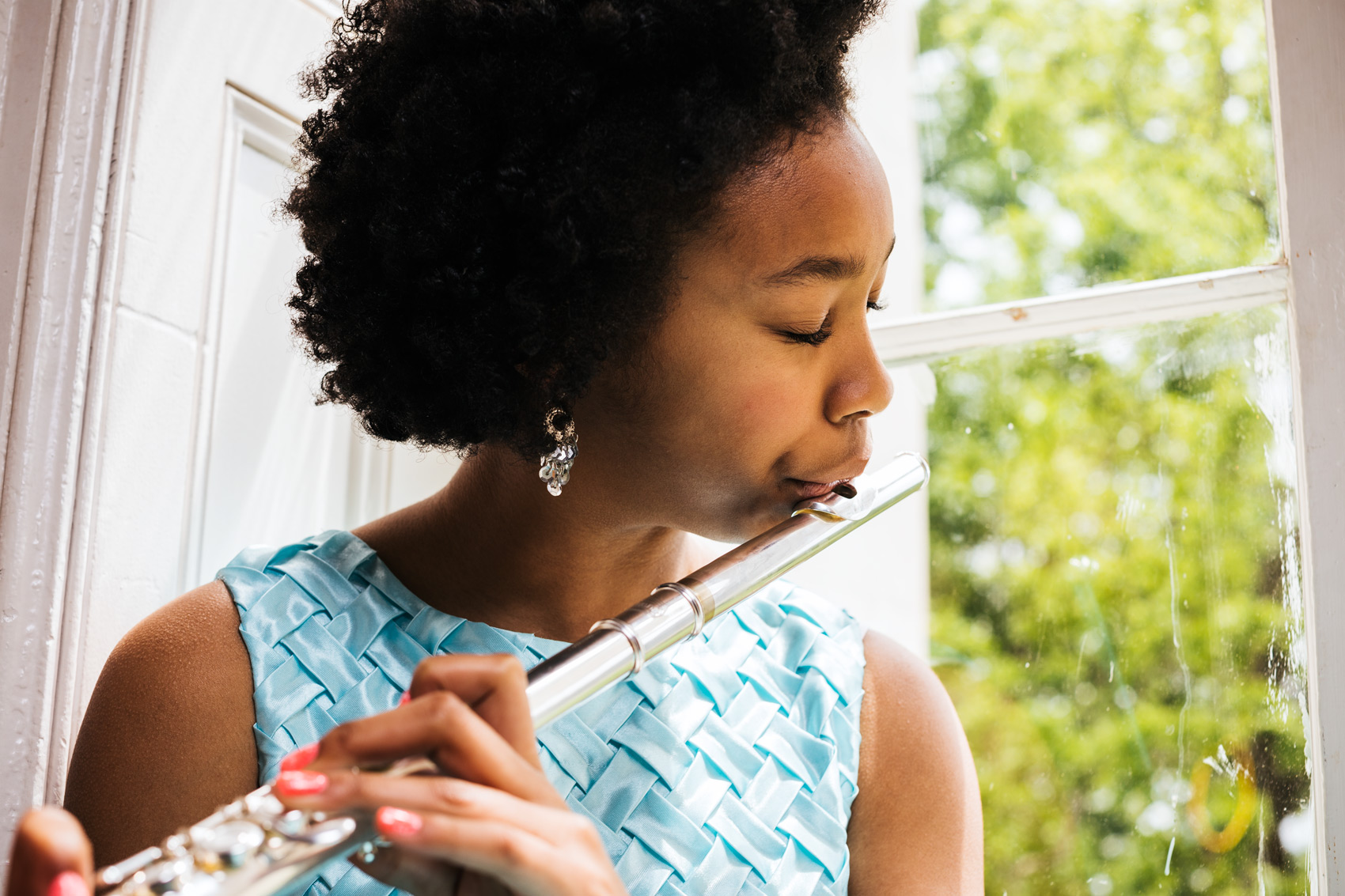tween girl playing flute by window, washington dc commercial photography