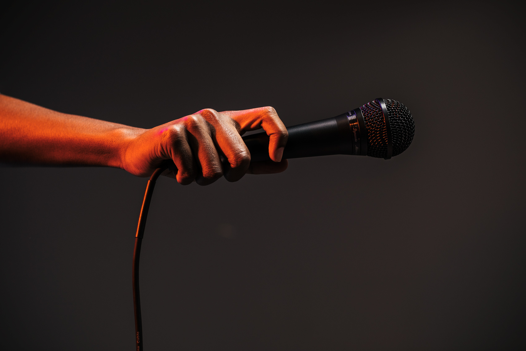 hand holding microphone under red light, washington dc commercial photography