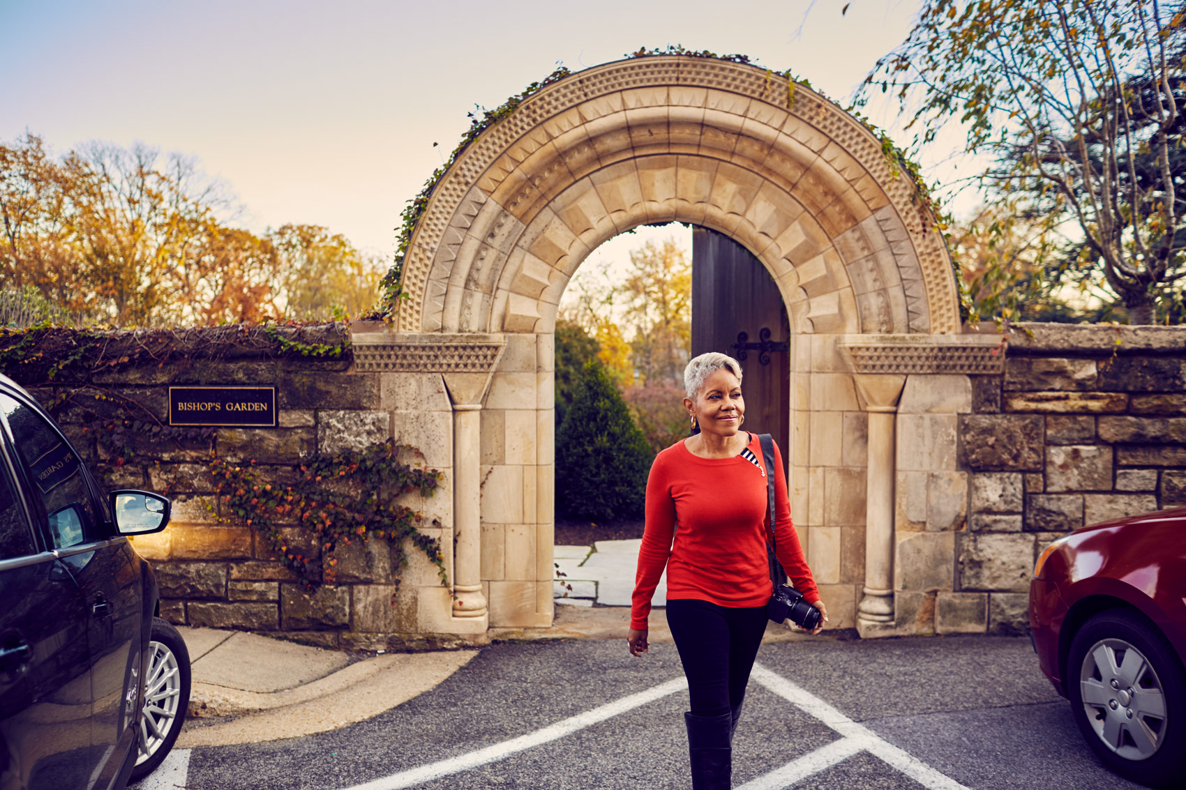 older woman with gray in red shirt walking in front of arch, washington dc commercial photography