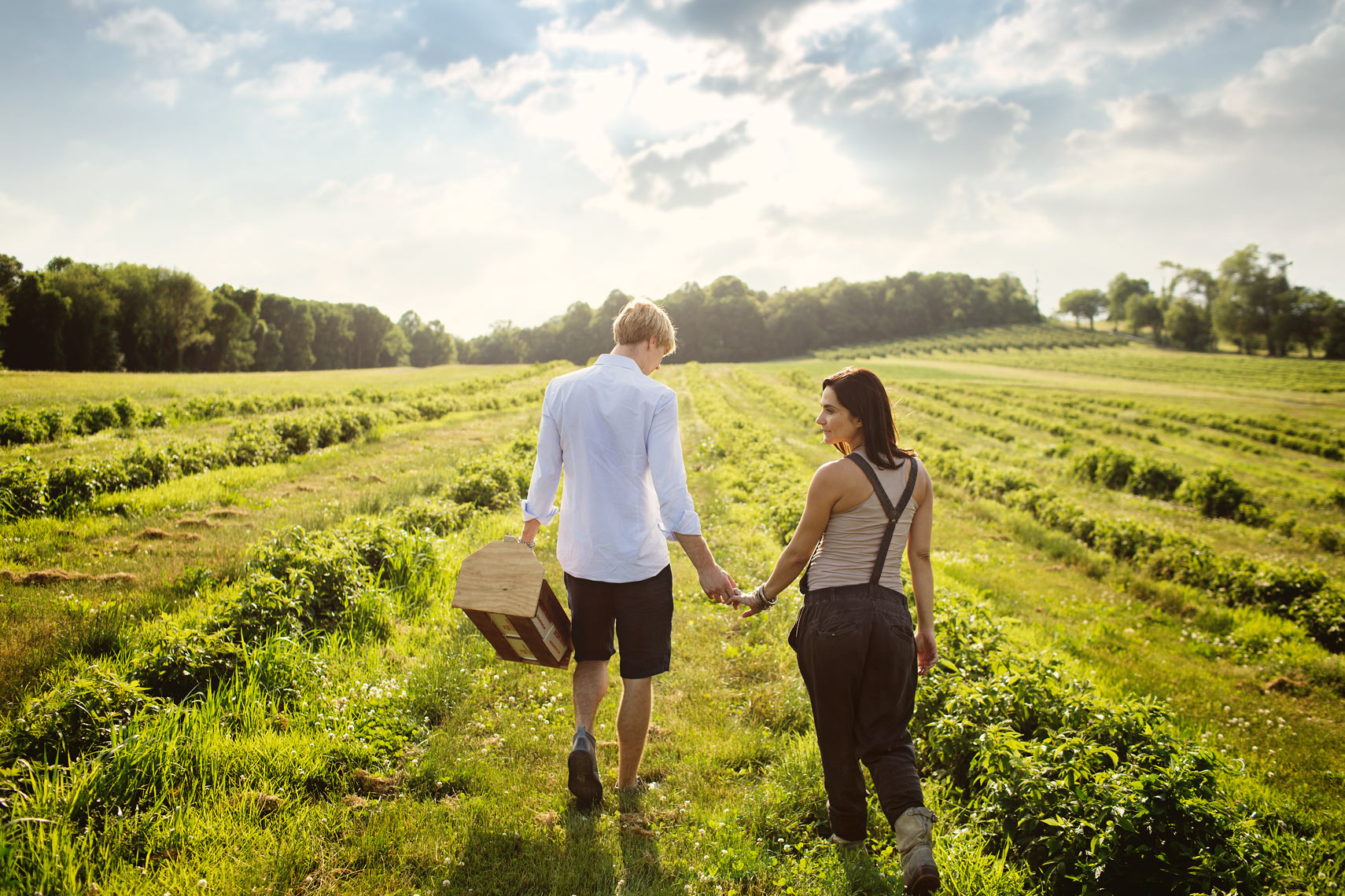 couple strawberry picking in field for washington dc commercial photography