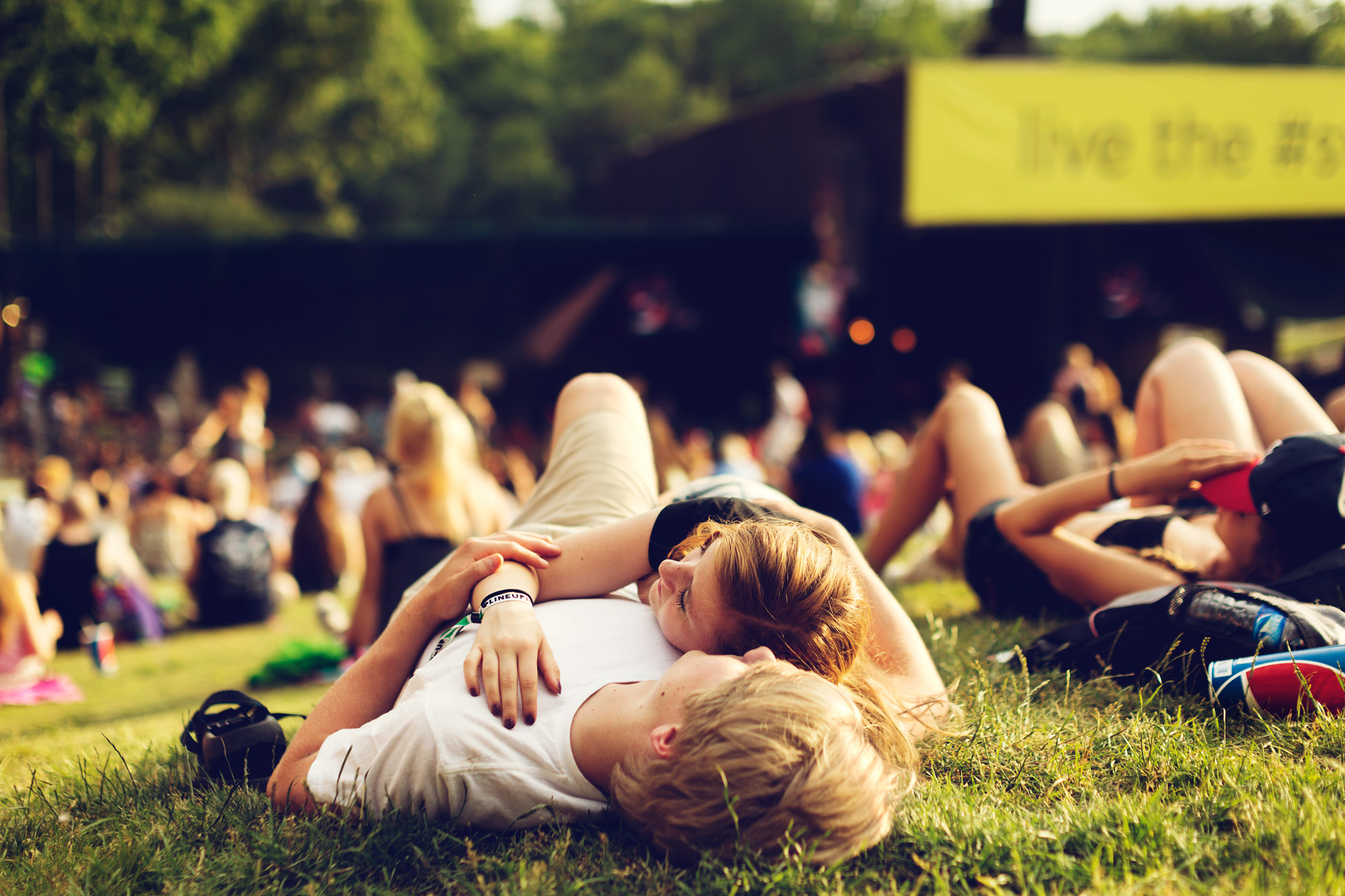 couple relaxing on grass at concert festival for washington dc editorial photography