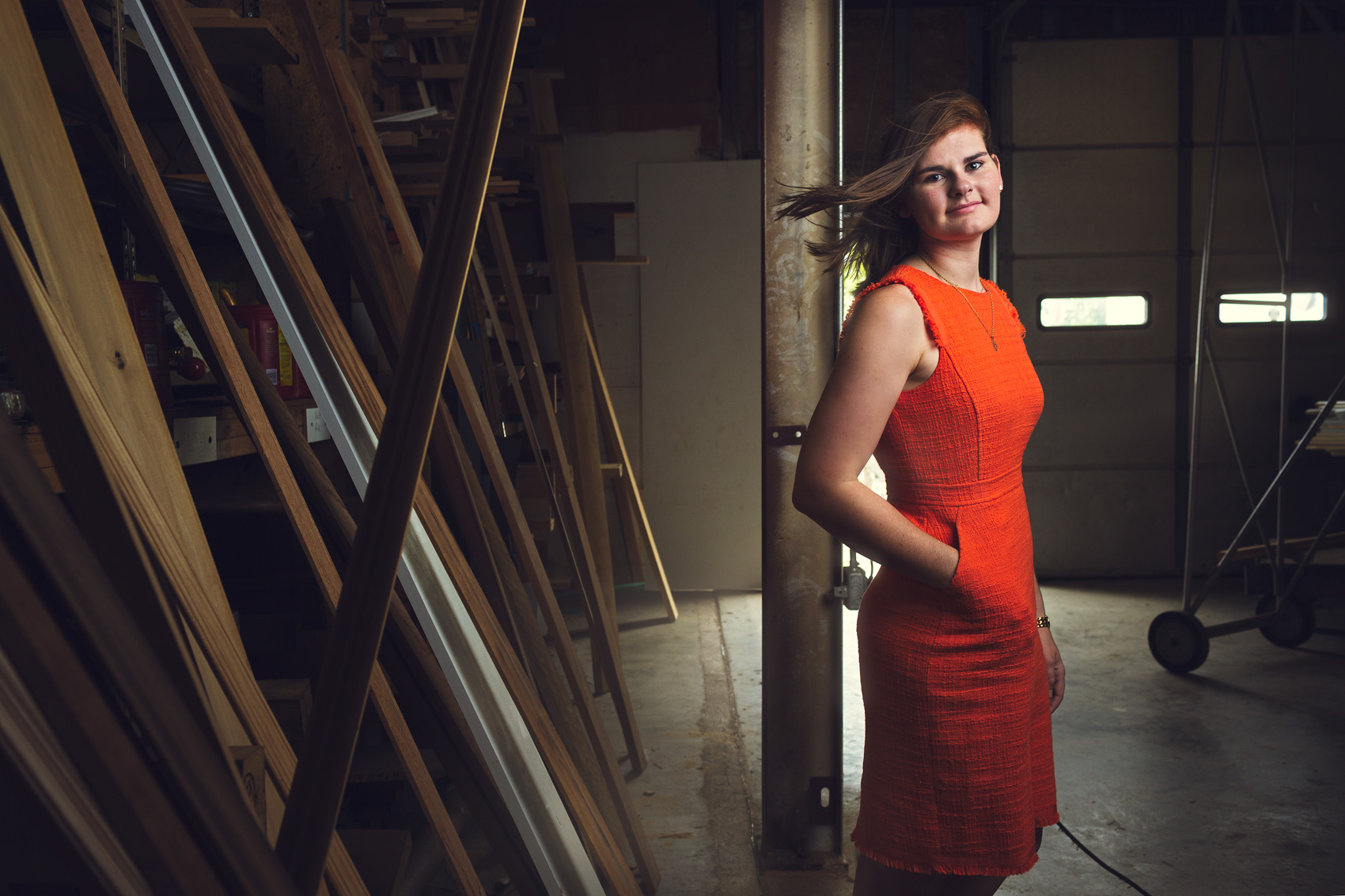 young woman in orange dress standing in lumber yard washington dc editorial photography