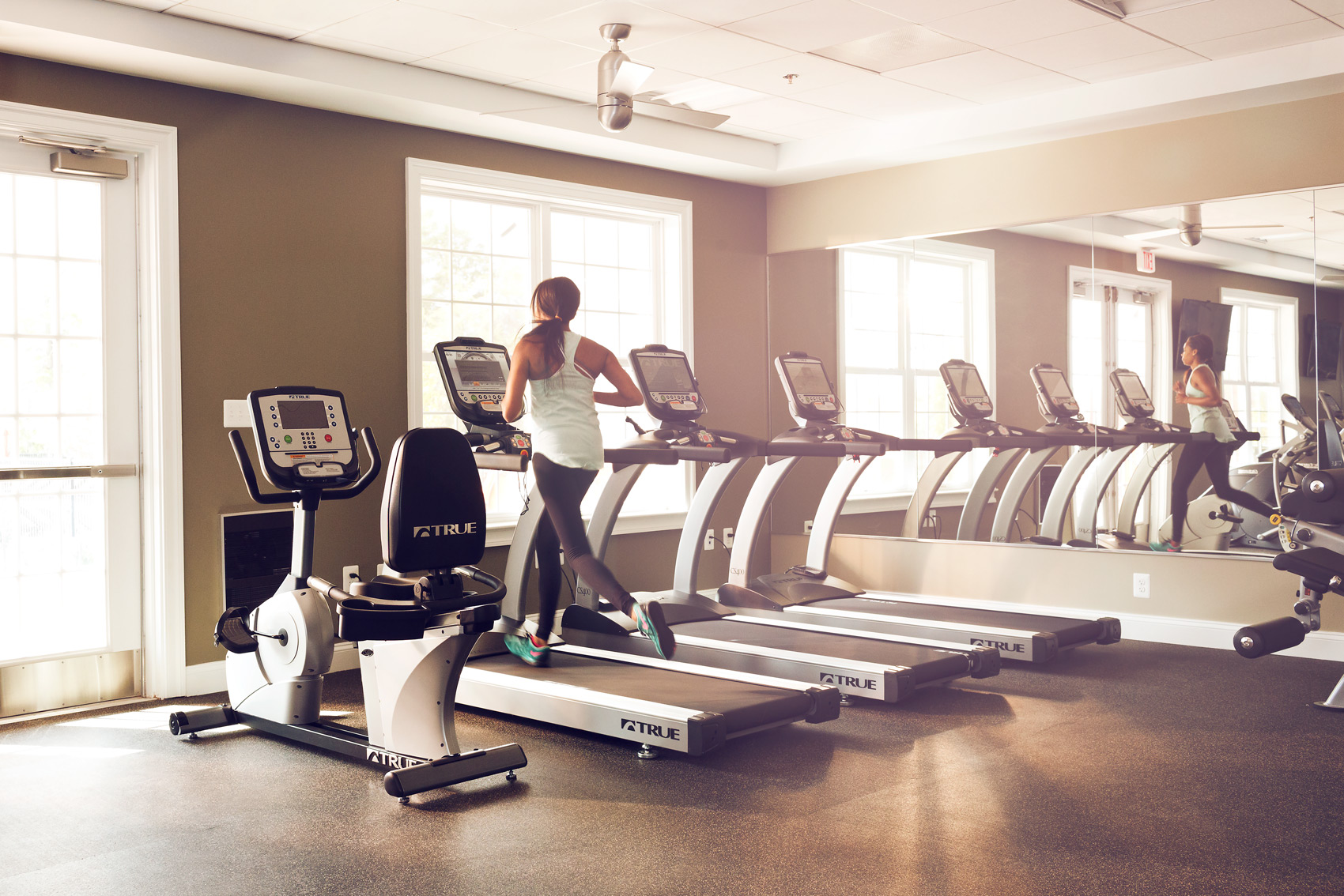woman runs on treadmill in gym for washington dc fitness photography
