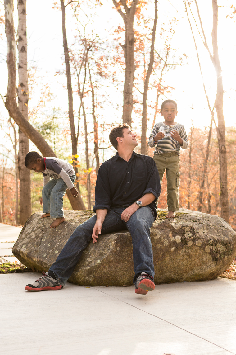 father sitting on rock with kids for washington dc editorial photography