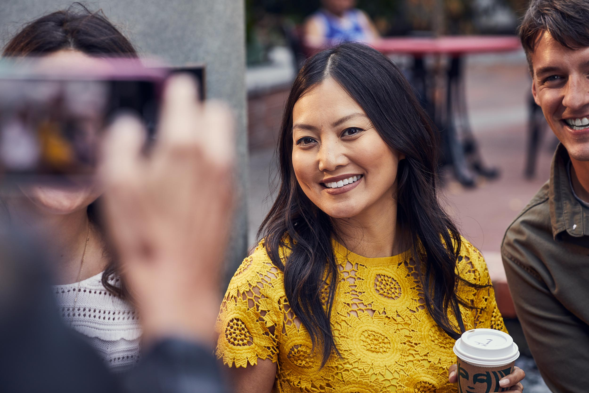 woman in yellow dress and friends smile for smartphone photo, washington dc commercial photography