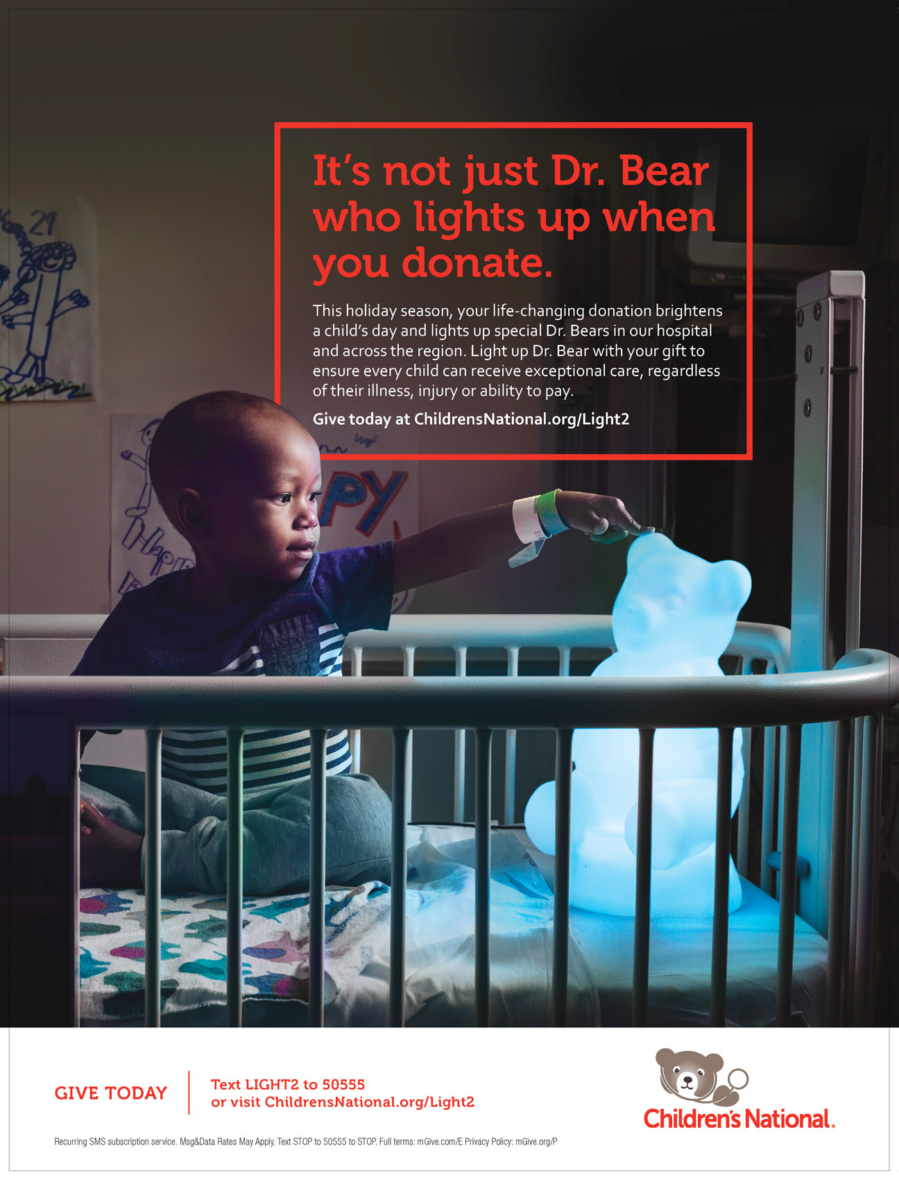 boy touching glowing bear in hospital bed for children