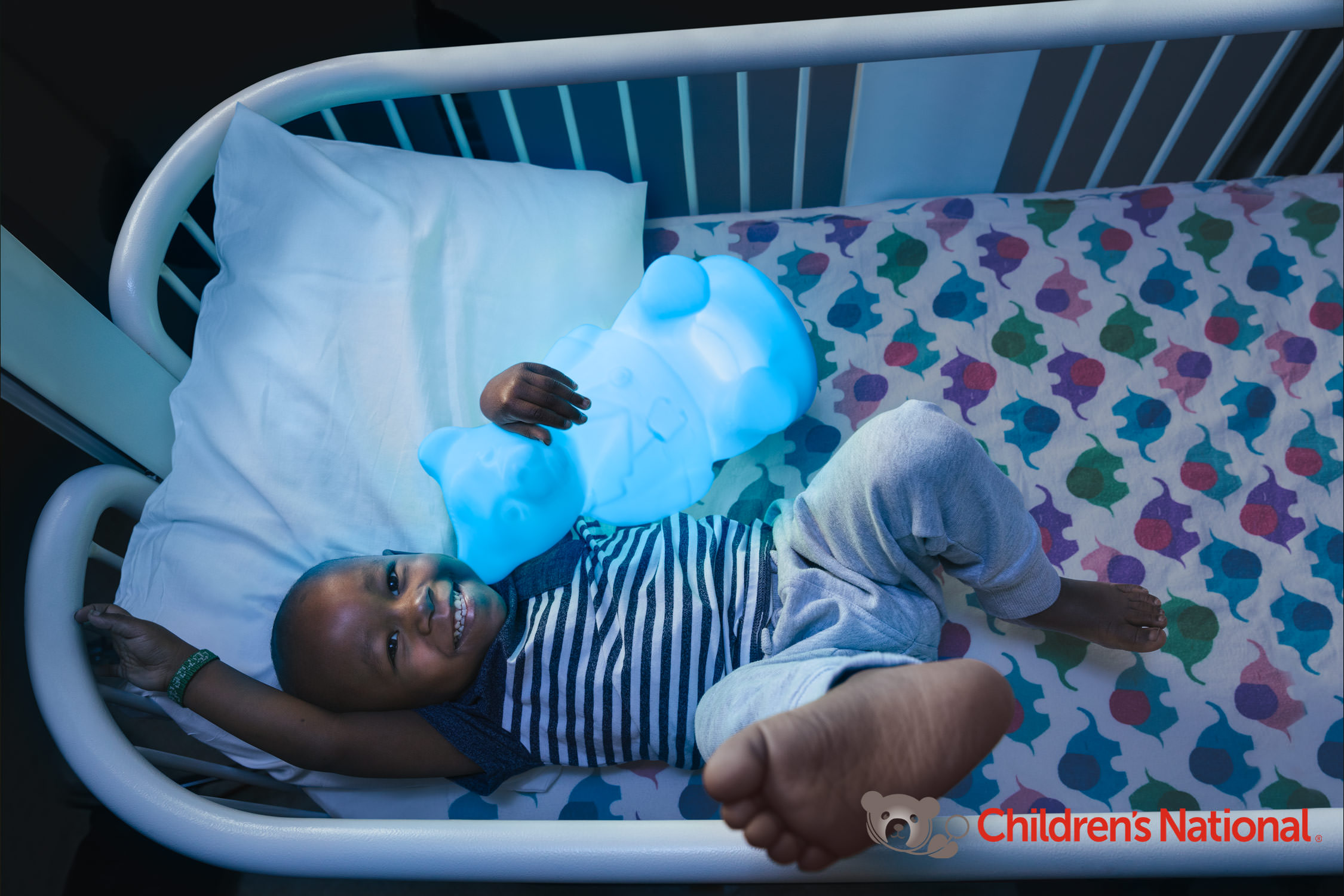 boy holding glowing bear in hospital bed, washington dc commercial photography