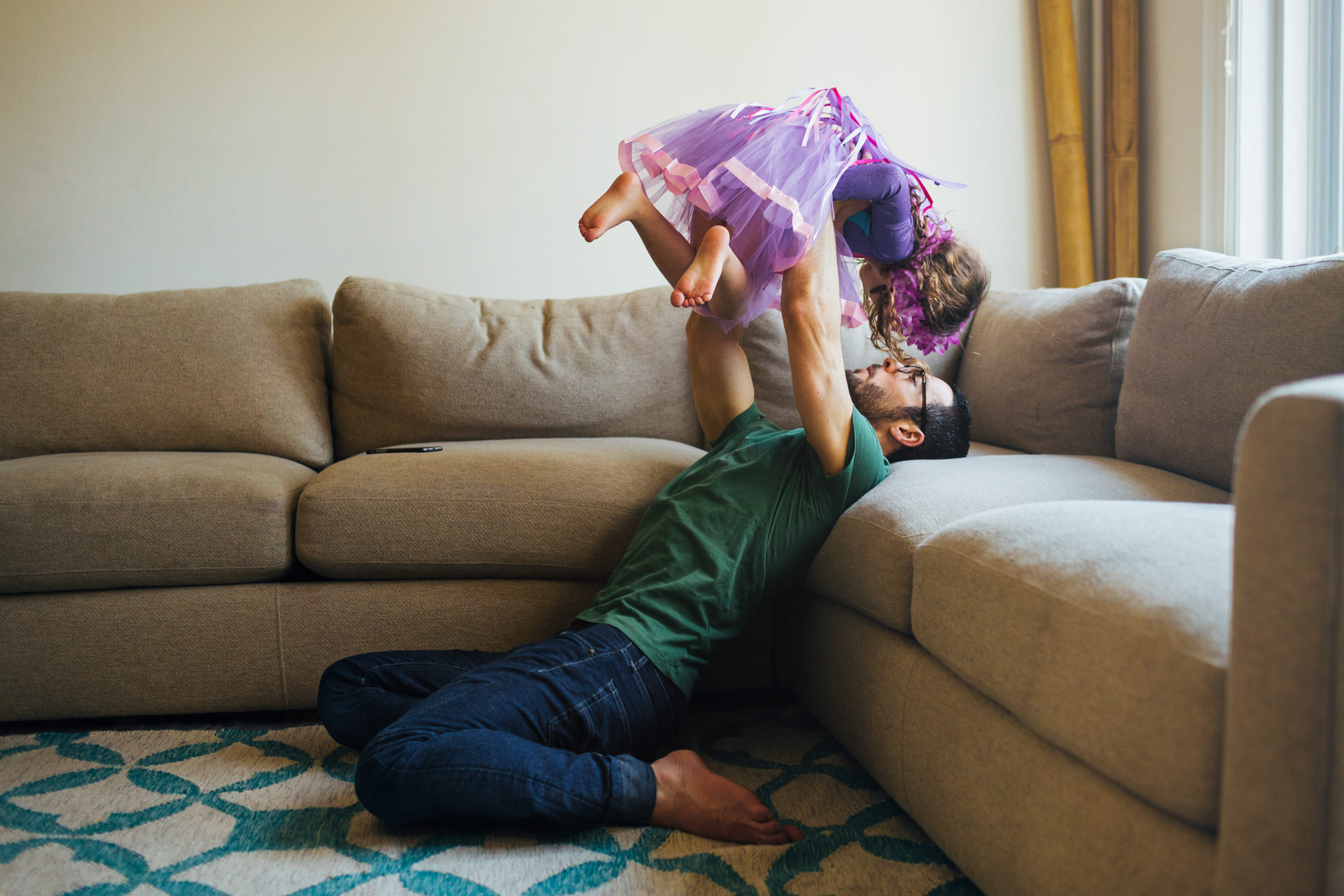 father holding up daughter near couch, washington dc commercial photography