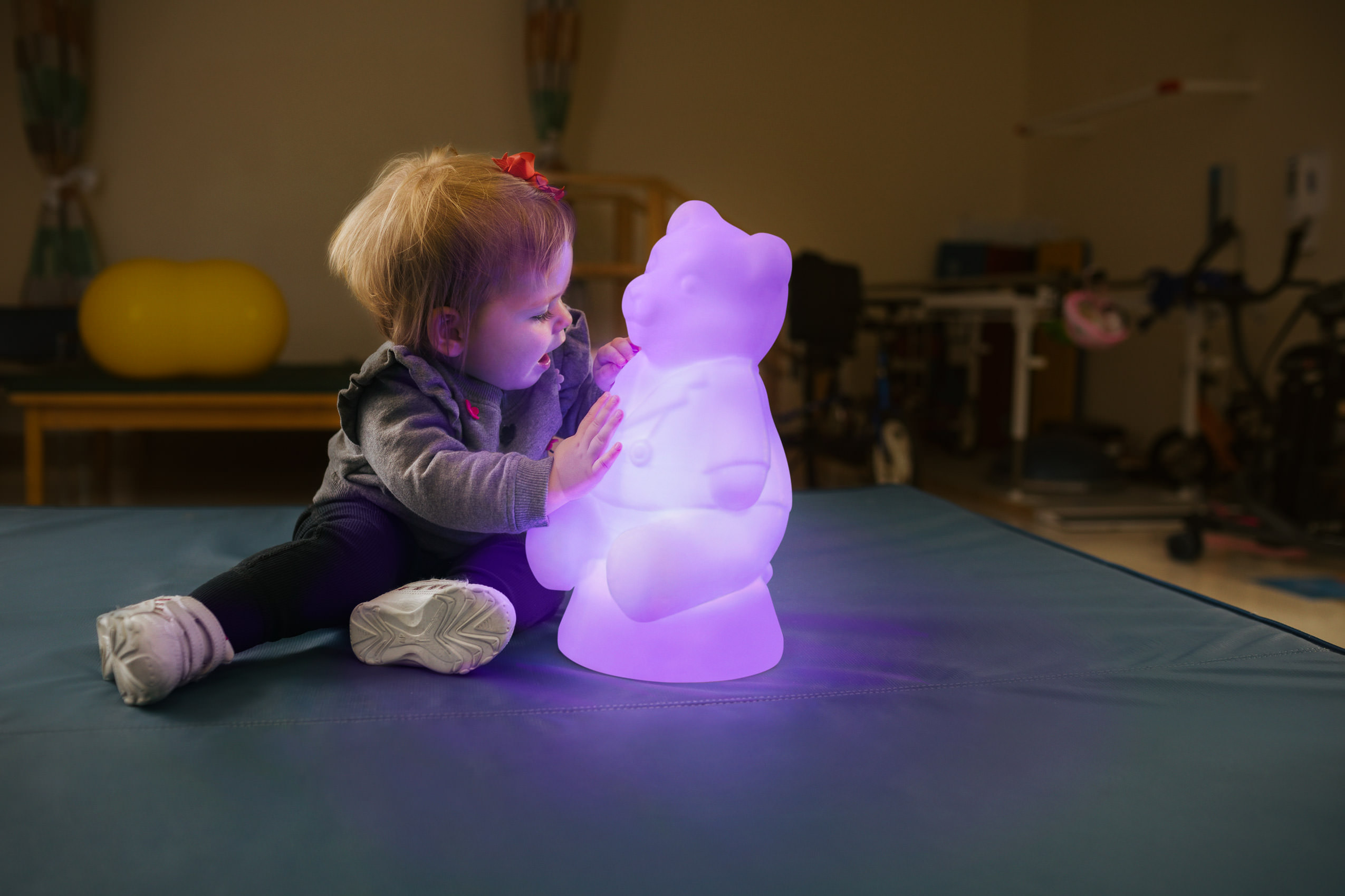 toddler with purple glowing bear in pt room for washington dc healthcare photography