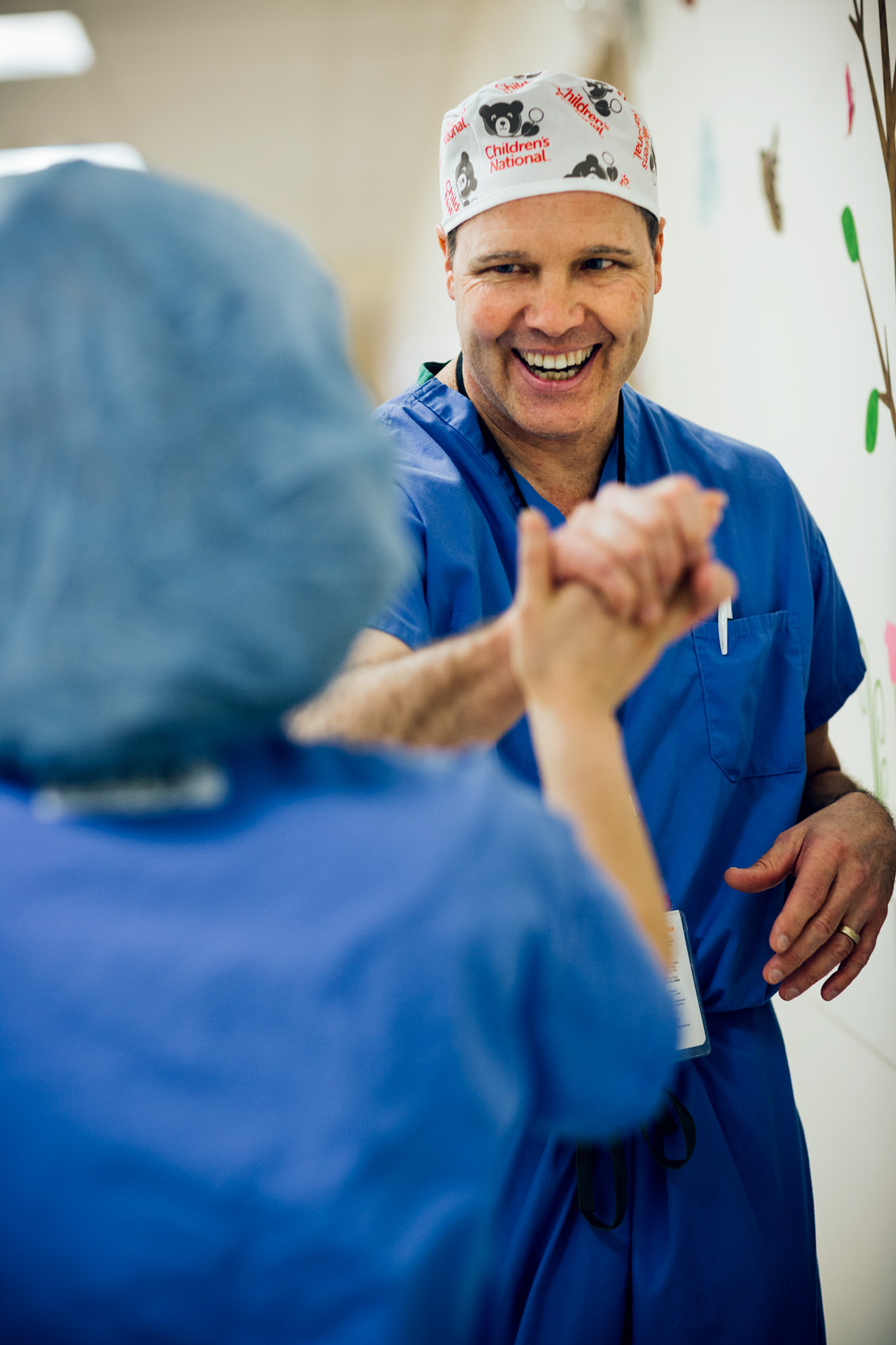 pediatric surgeon high fiving aid, washington dc healthcare photography