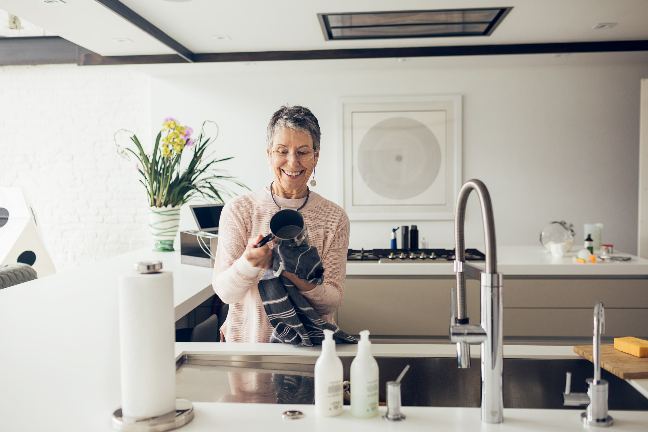 older woman washing dishes in kitchen, washington dc commercial photography